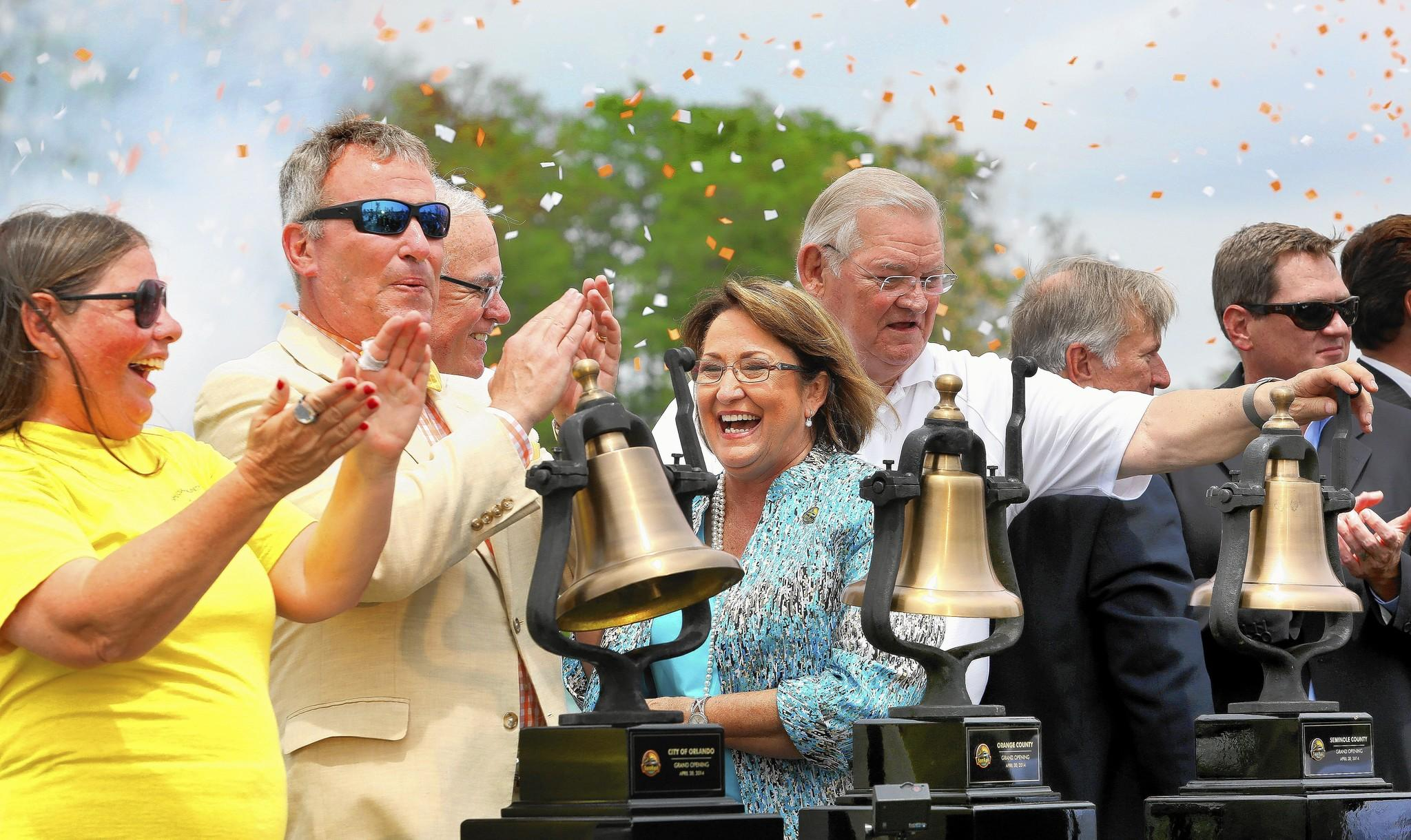 The long-awaited moment finally arrives with bell-ringing and confetti during the official SunRail Grand Opening Ceremony at the Sand Lake Road Station, in Orlando, Wednesday, April 30, 2014. From left, JoAnne Counelis, a guest of Orlando mayor Buddy Dyer, former Orange mayor Rich Crotty, current Orange mayor Teresa Jacobs, Orange commissioner Fred Brummer, and other elected officials.