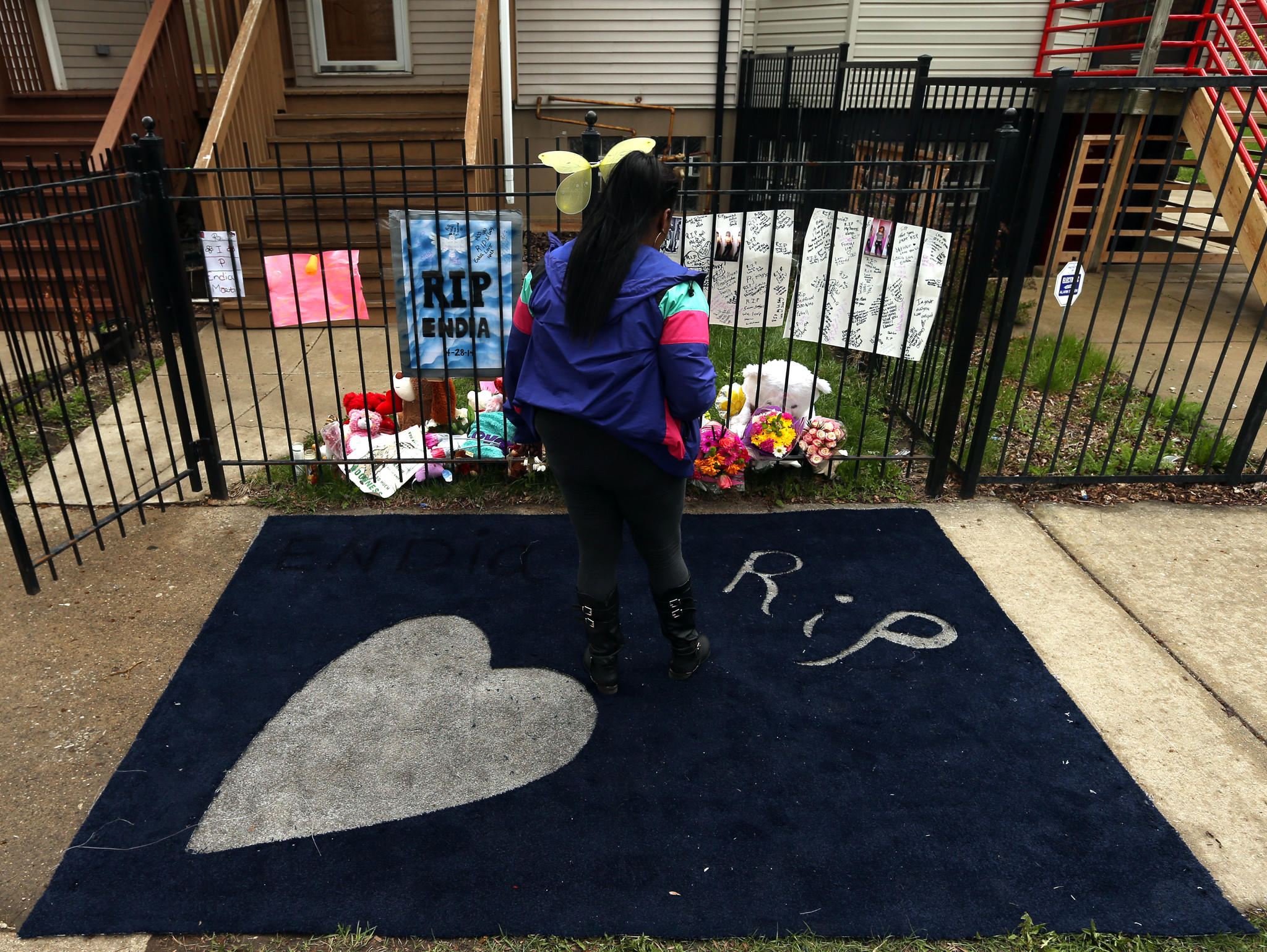 Michelle Warr stops in the 900 block of West Garfield Boulevard in Chicago on Thursday, May 1, 2014, at the memorial for Endia Martin.