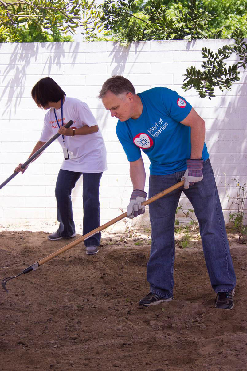 Experian employees Neddy Daquiz, left, and Kevin McBride volunteer at Girls Inc. of Orange County in Costa Mesa on April 22 for an Earth Day event.