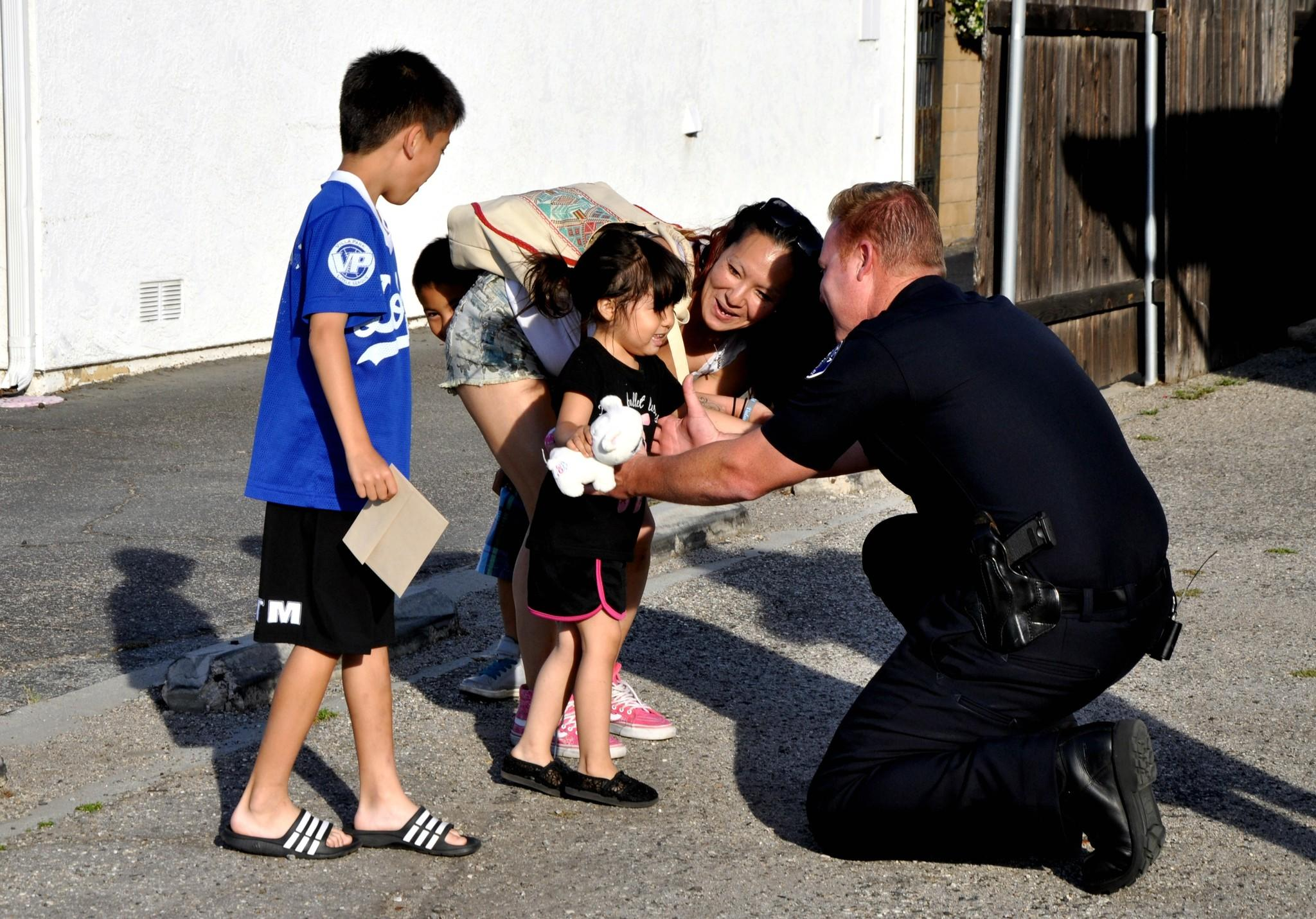 Costa Mesa Police Department Officer Matt Olin is reunited with Sara Villasenor, the mother of 4-year-old Nina, whom Olin rescued from near drowning on Monday.