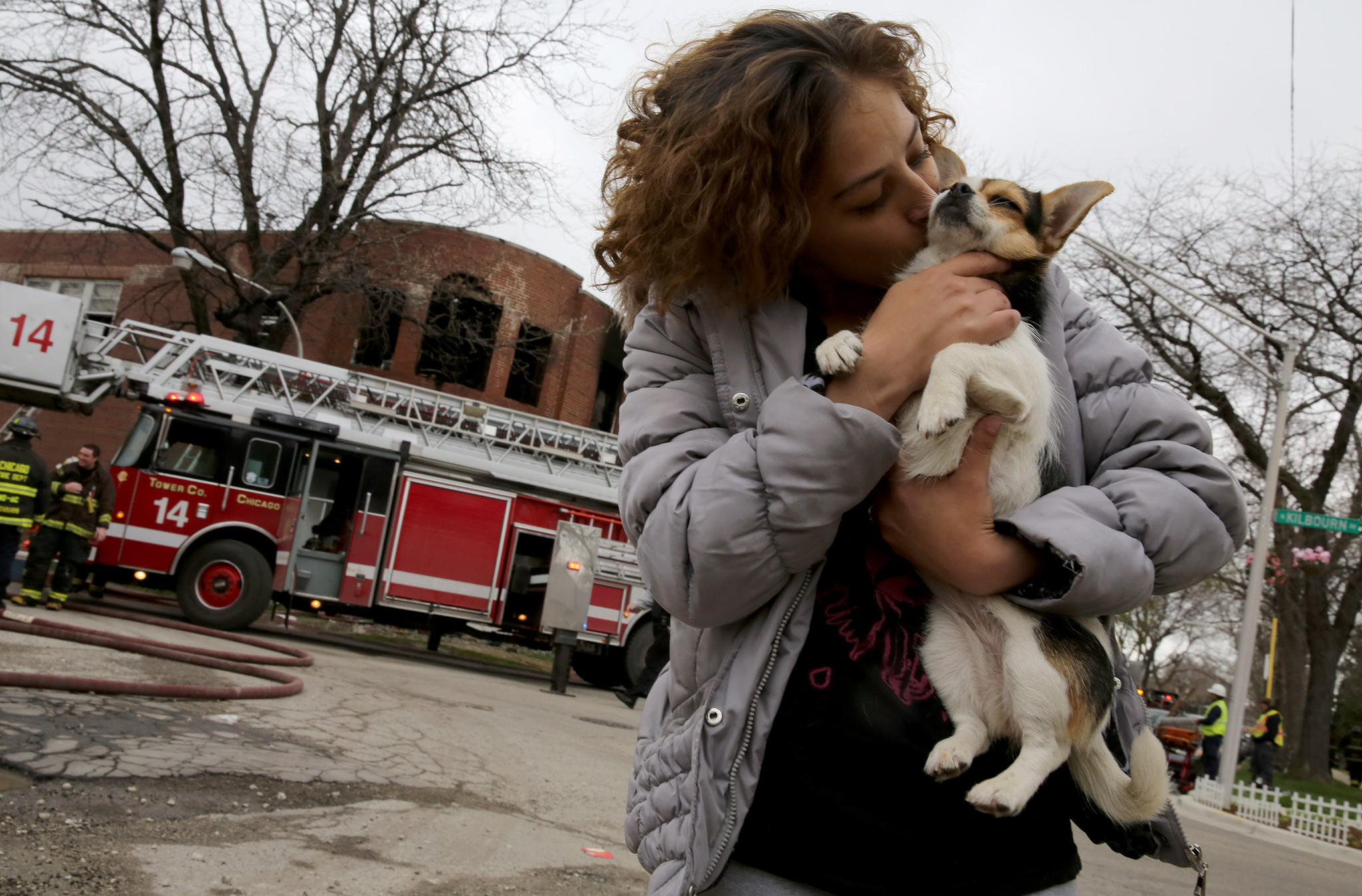 "Amanda Lozada comforts her dog ""Flower"" after Lozada and her family fled their apartment following a two alarm fire in the second floor apartments of a corner building in the 4400 block of west Haddon Ave., in Chicago."