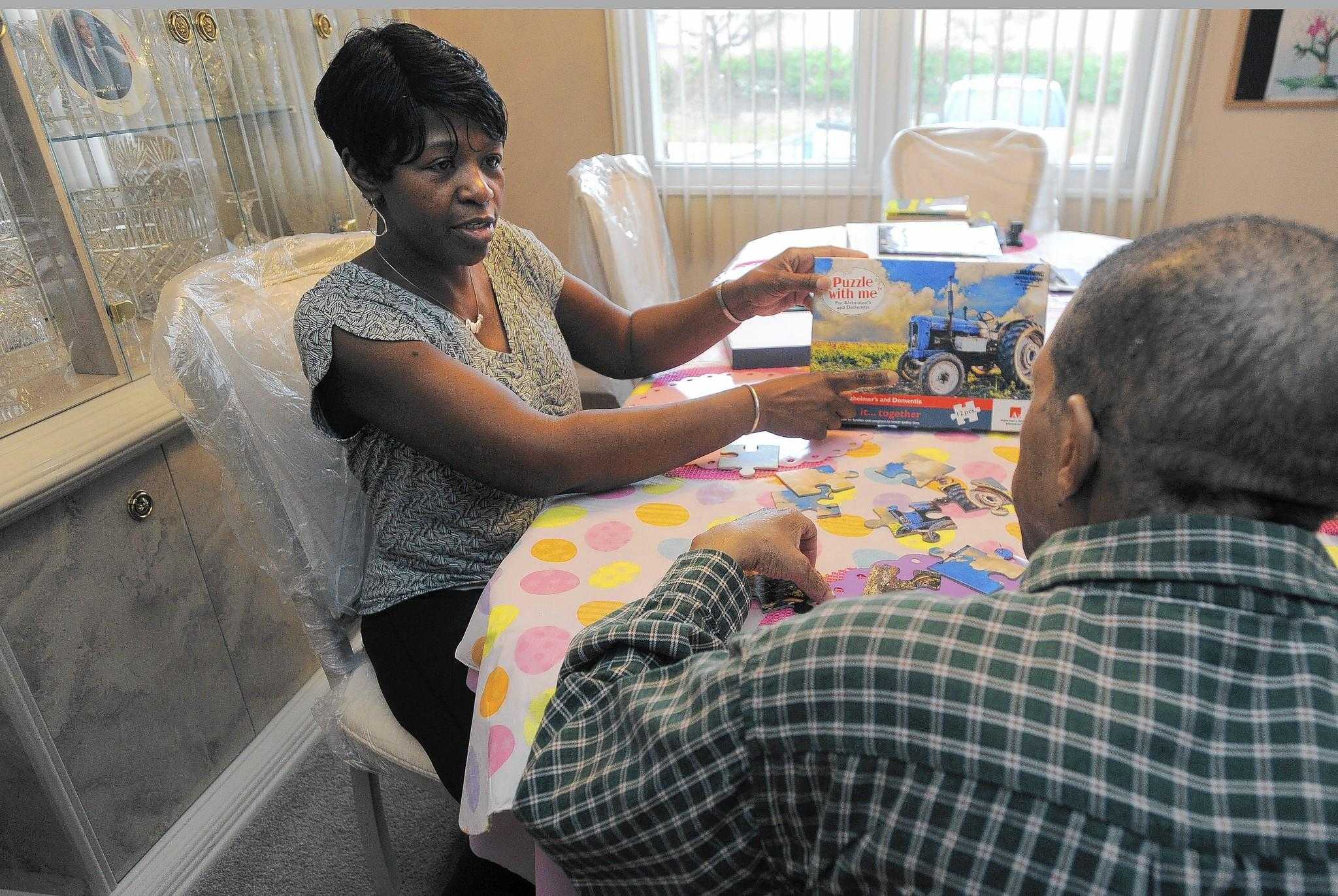 Wanda WIlliams, care provider and manager, Forever Care, Inc., talks with one of the three veterans she cares for in her home as they put a puzzle together.