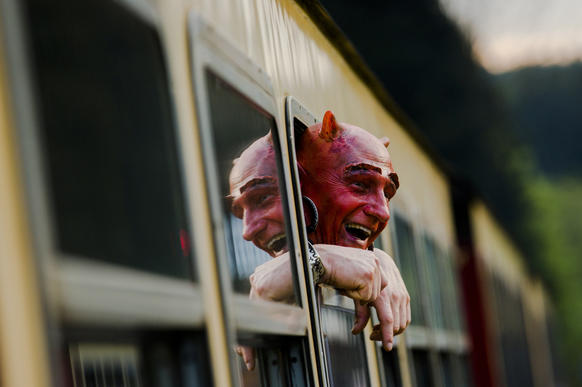 Man with a devil make-up looks out of a HSB light railway carriage as he travels through the Harz mountains to celebrate the Walpurgisnacht pagan festival, April 30, 2014. Legend has it that on Walpurgisnacht or May Eve, witches fly their broomsticks to meet the devil at the summit of the Brocken Mountain in Harz. In towns and villages scattered throughout the mountain region, locals make bonfires, dress in devil or witches costumes and dance into the new month of May. Picture taken April 30, 2014.  REUTERS/Thomas Peter (GERMANY - Tags: SOCIETY TRANSPORT TPX IMAGES OF THE DAY) - RTR3ND3P