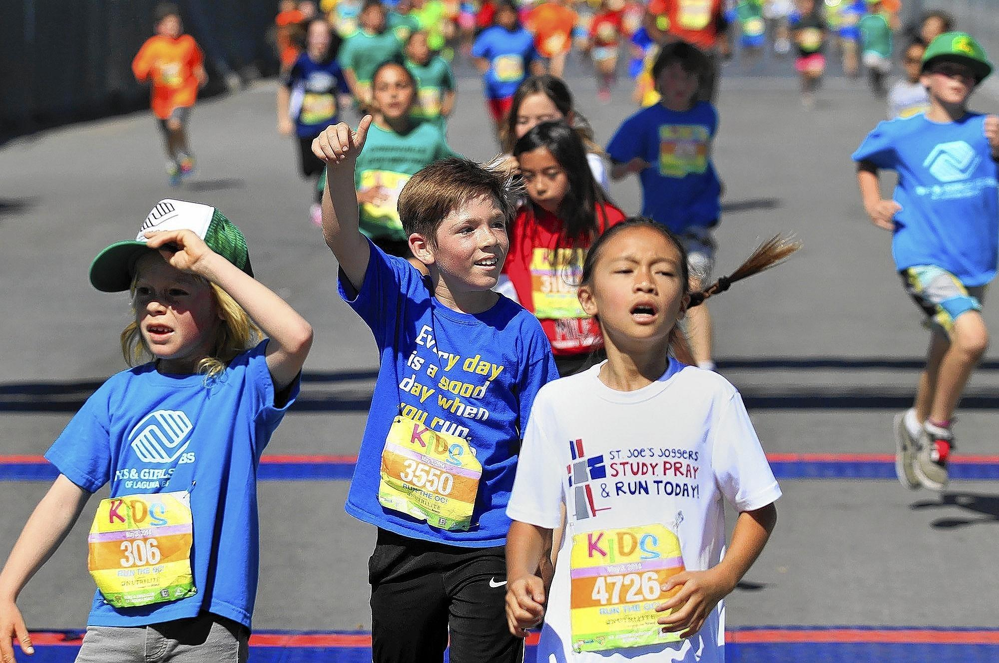 Gavin Yauchzee, 9, center, of Moffett Elementary school in Huntington Beach gives a thumbs up after finishing in the 2014 Kids Run the OC marathon held at the OC Fairgrounds on Saturday.