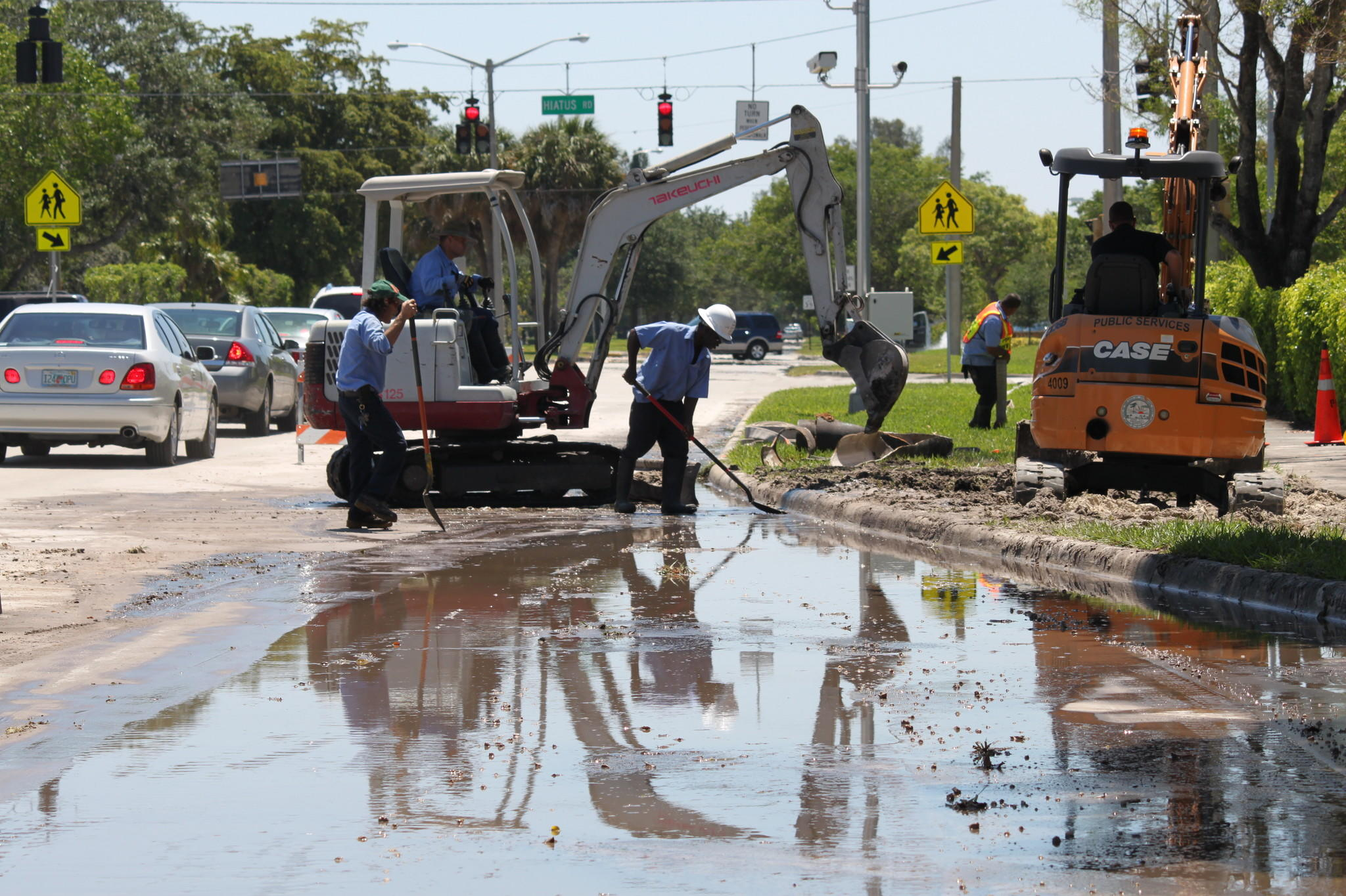 Crews from Pembroke Pines' utilities department clean up the mess after a 12-inch water main ruptured Sunday, flooding parts of the intersection at Taft Street and Hiatus Road. Water pressure dropped after the 7 am break, but service to area homes and businesses not interrupted, said utilities supervisor Steve Stanton. All lanes reopened by about 1 p.m.