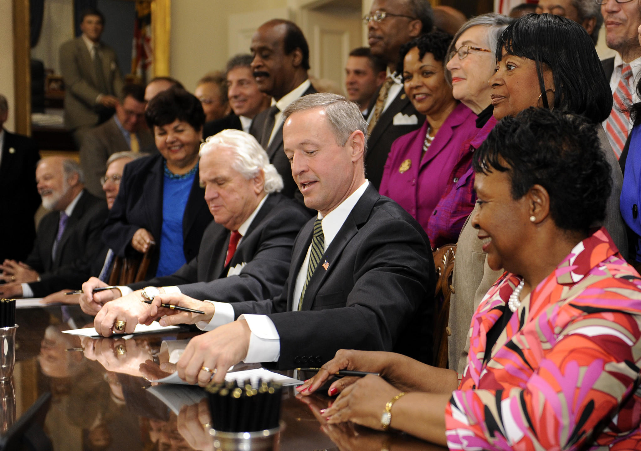 Seated at table left to right as the minimum wage bill is signed into law at the State House in Annapolis: Senate President Thomas V. Mike Miller Jr., Governor Martin O'Malley, Speaker Pro Tem of the House of Delegates Adrienne Jones.