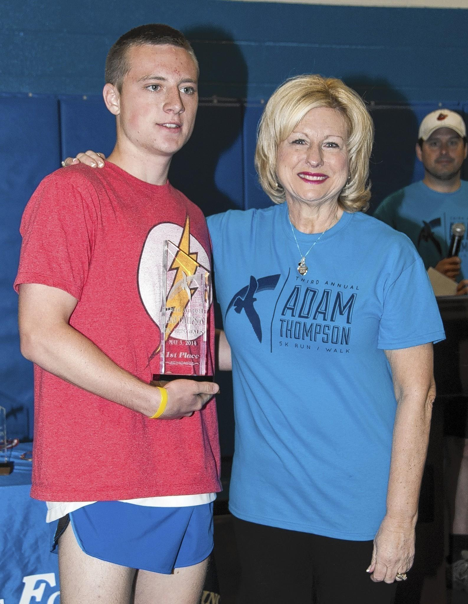 Pat Thompson, right, mother of the late Adam Thompson, stands with Tyler Muse, who finished first in Saturday's third annual Adam Thompson 5K Run/Walk at Harford Community College. Muse completed the run in 16:44.5.