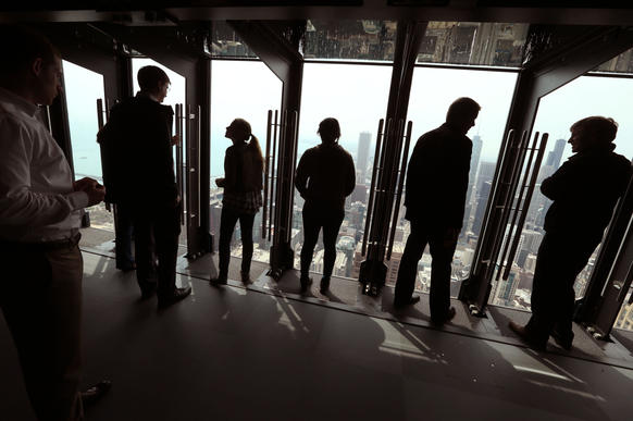 """The John Hancock Observatory will open a new attraction called """"Tilt!"""" which has viewers stand against one of 8 glass panels that tilt out and down on an angle from the observatory."""
