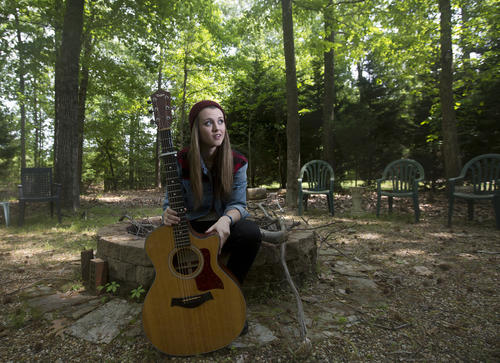 """Smithfield's Bria Kelly, 18, sits with her guitar in her backyard on Wednesday afternoon. Kelly returned home last week after she was eliminated by viewer vote on NBC's """"The Voice."""""""