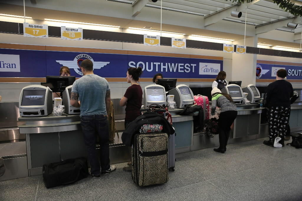 Travelers wait at the Southwest check in counter at Midway Airport in January.