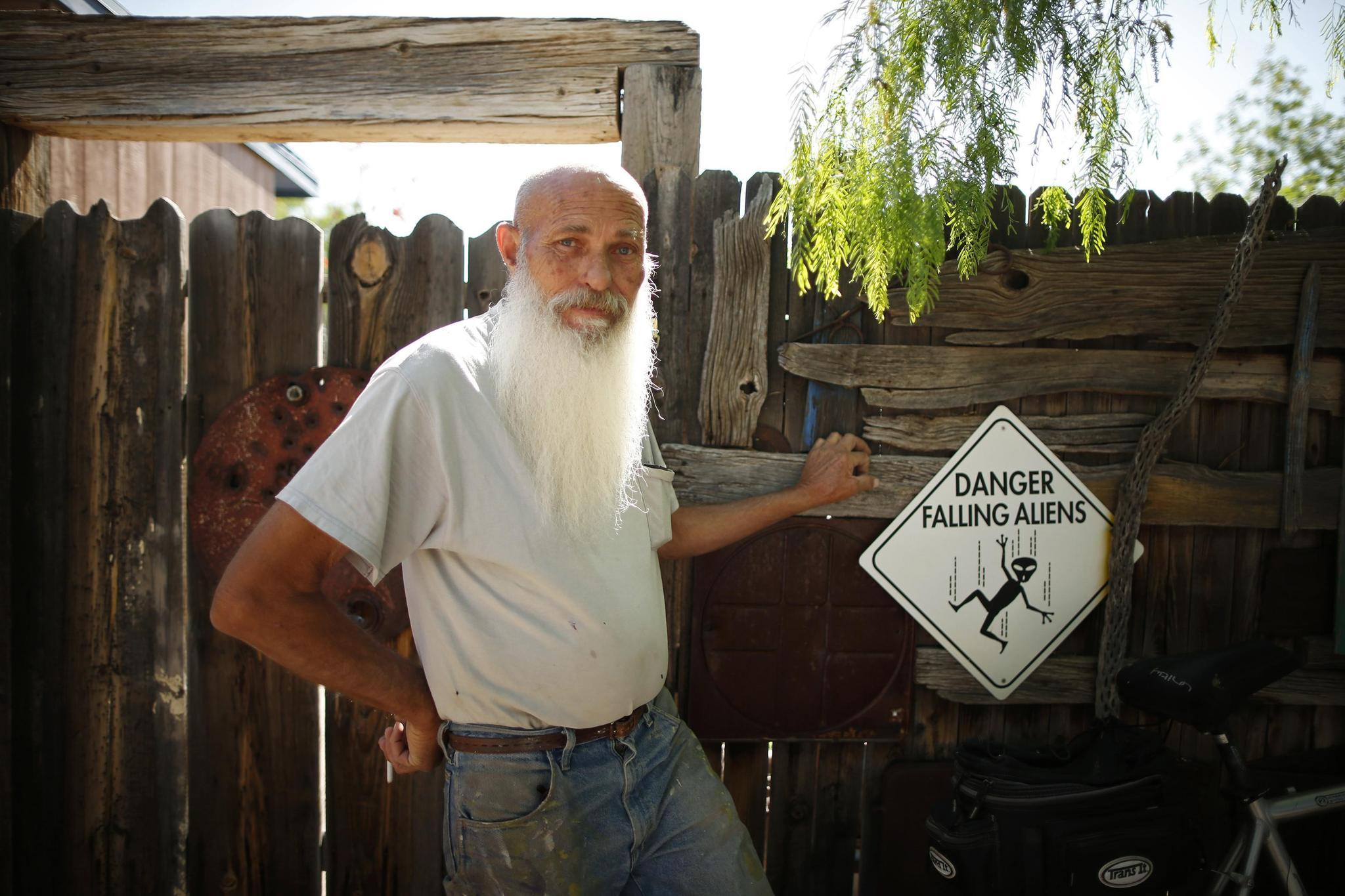 Artist Roy Lohr, 69, stands by a sign at his home in Truth or Consequences, New Mexico May 2.