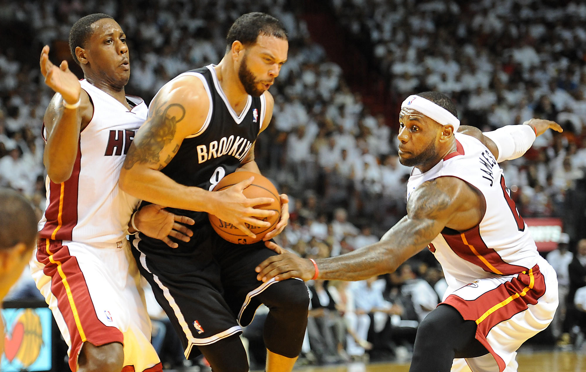 The Miami Heat host the Brooklyn Nets at American Airlines Arena for game two of the Eastern Conference semi-finals. Brooklyn's Deron Williams tries to squeeze between the defense of Mario Chalmers and LeBron James.