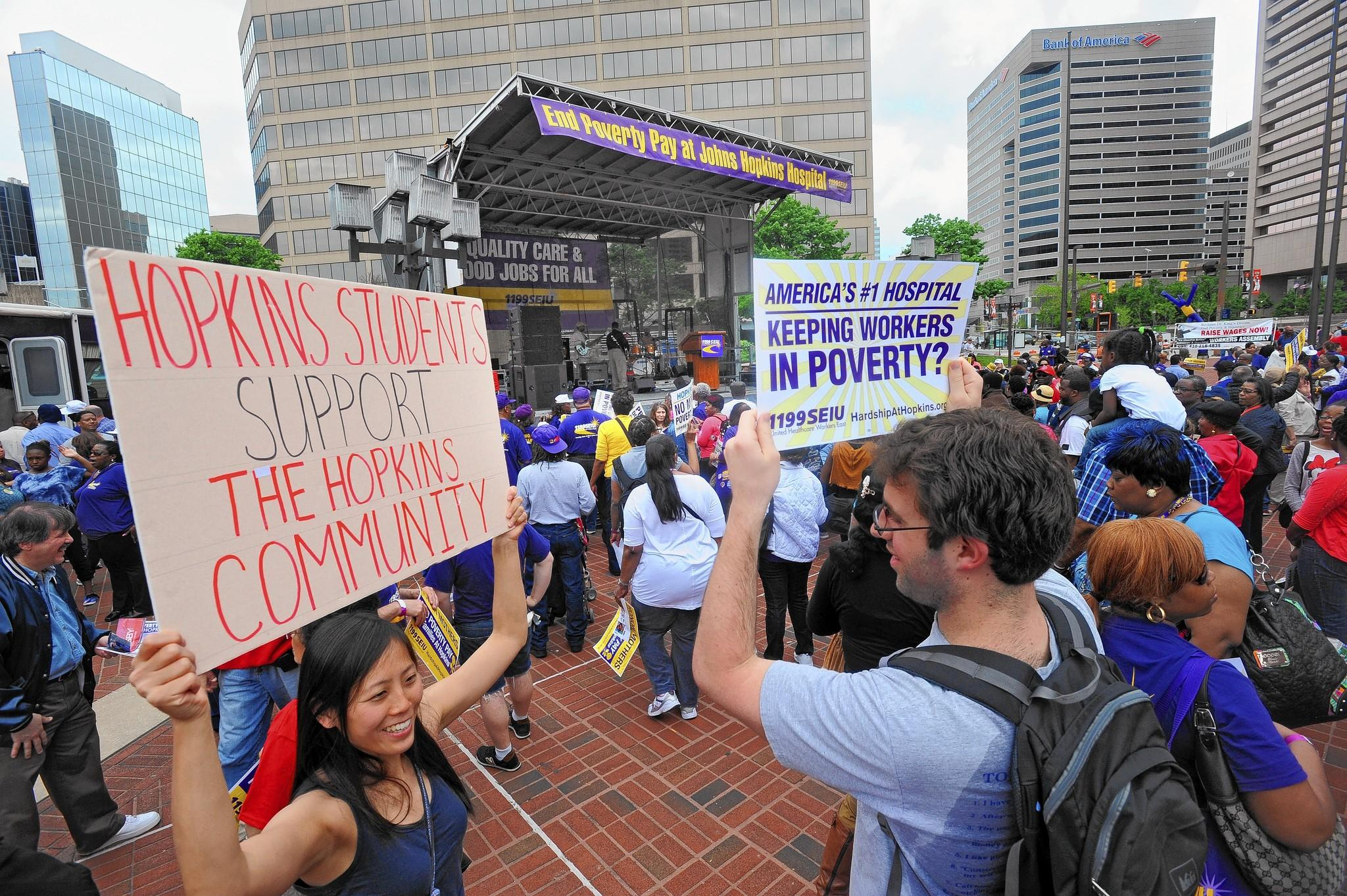 Johns Hopkins Medical School students Yukyan Lam, left, and Tyler Smith are among the thousands of union supporters rallied at Inner Harbor's McKeldin Square to fight for increase wages for the service, maintenance and technical employees at Johns Hopkins Hospital.