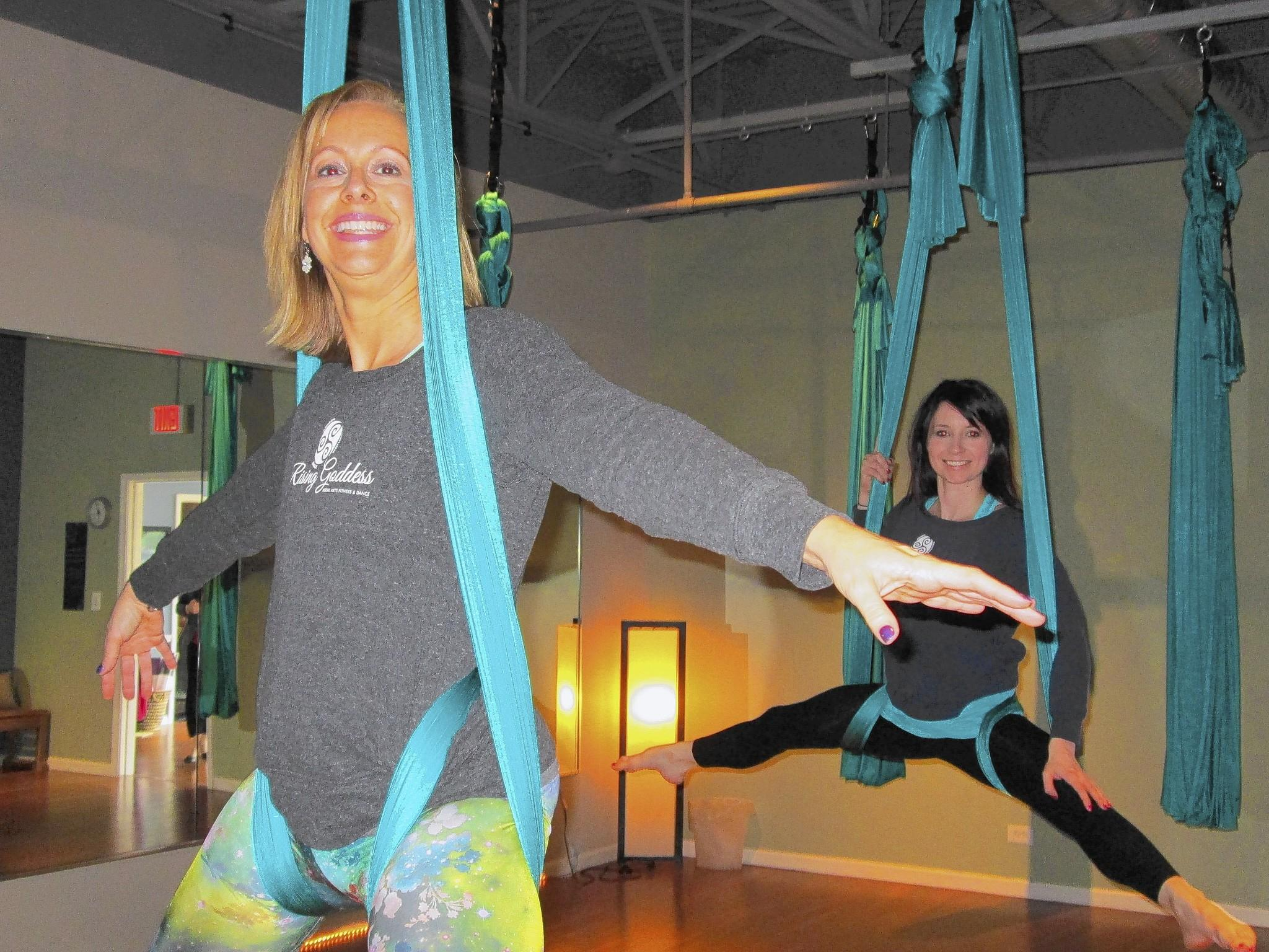 Barb Cassidy (front) and Michelle Tenuta (back) stretch on a hammock at their new aerial arts and fitness studio in Westmont.
