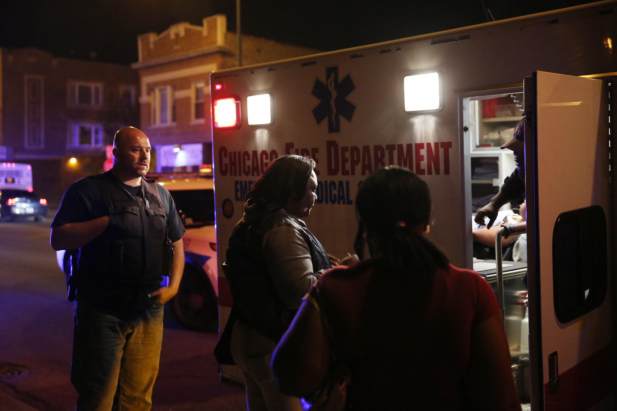 A person is taken by ambulance from the scene where a 32-year-old man and a 22-year-old woman were each shot in the leg on Saturday night near the intersection of South Cicero Avenue and West Congress Parkway in Chicago.