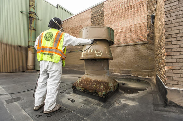 The Chicago Department of Streets & Sanitation removing graffiti at a factory on the West Side on May 7, 2014.