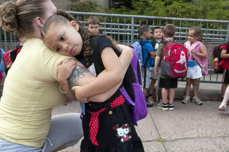 After arriving by bus at Naubuc Elementary School in Glastonbury for her first day of kindergarten, Takia Peau, 5, hugs her mom Amy Jones, who followed the bus to see her daughter arrive.