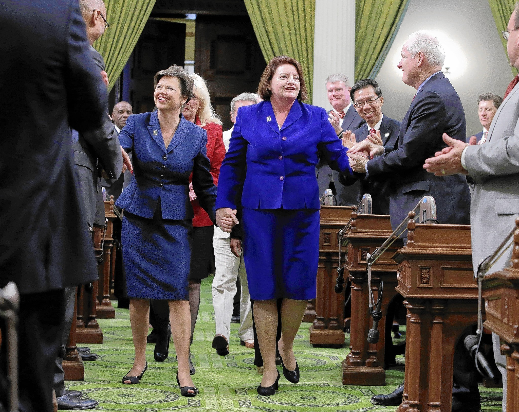 Toni Atkins (D-San Diego), right, walks hand in hand with her spouse, Jennifer LeSar, to the rostrum when she was elected as Assembly speaker in 2014. She will be the next leader of the Senate. (Associated Press)