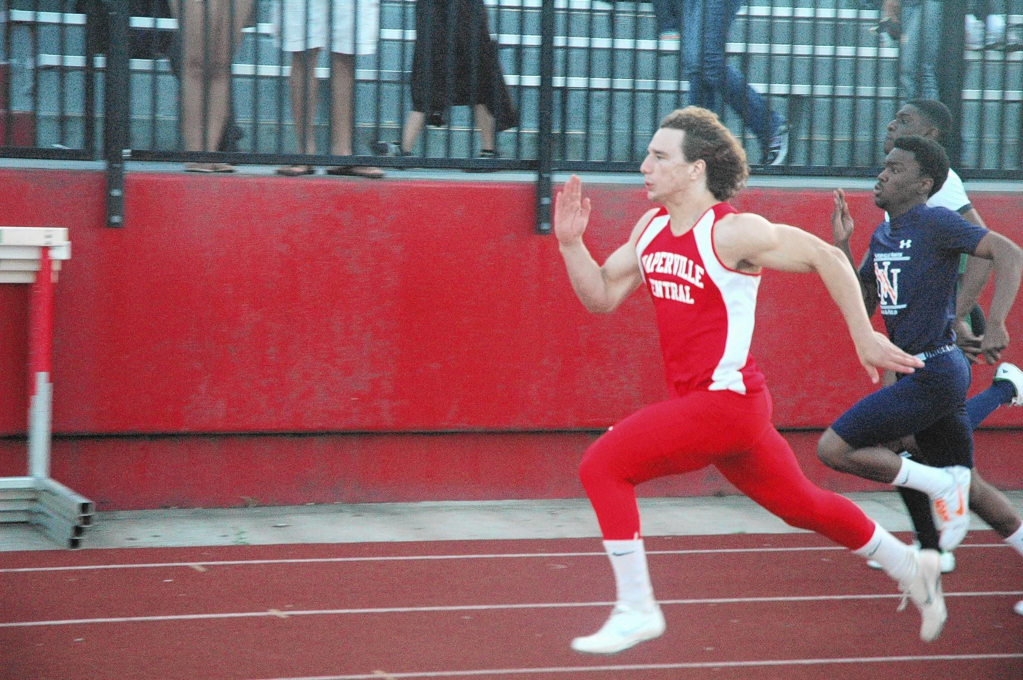 Naperville Central senior Ben Andreas competes in the 100-meter run at the DuPage County meet at Naperville Central on Friday night. He finished sixth in the 100 meters and won the triple jump for the Redhawks.