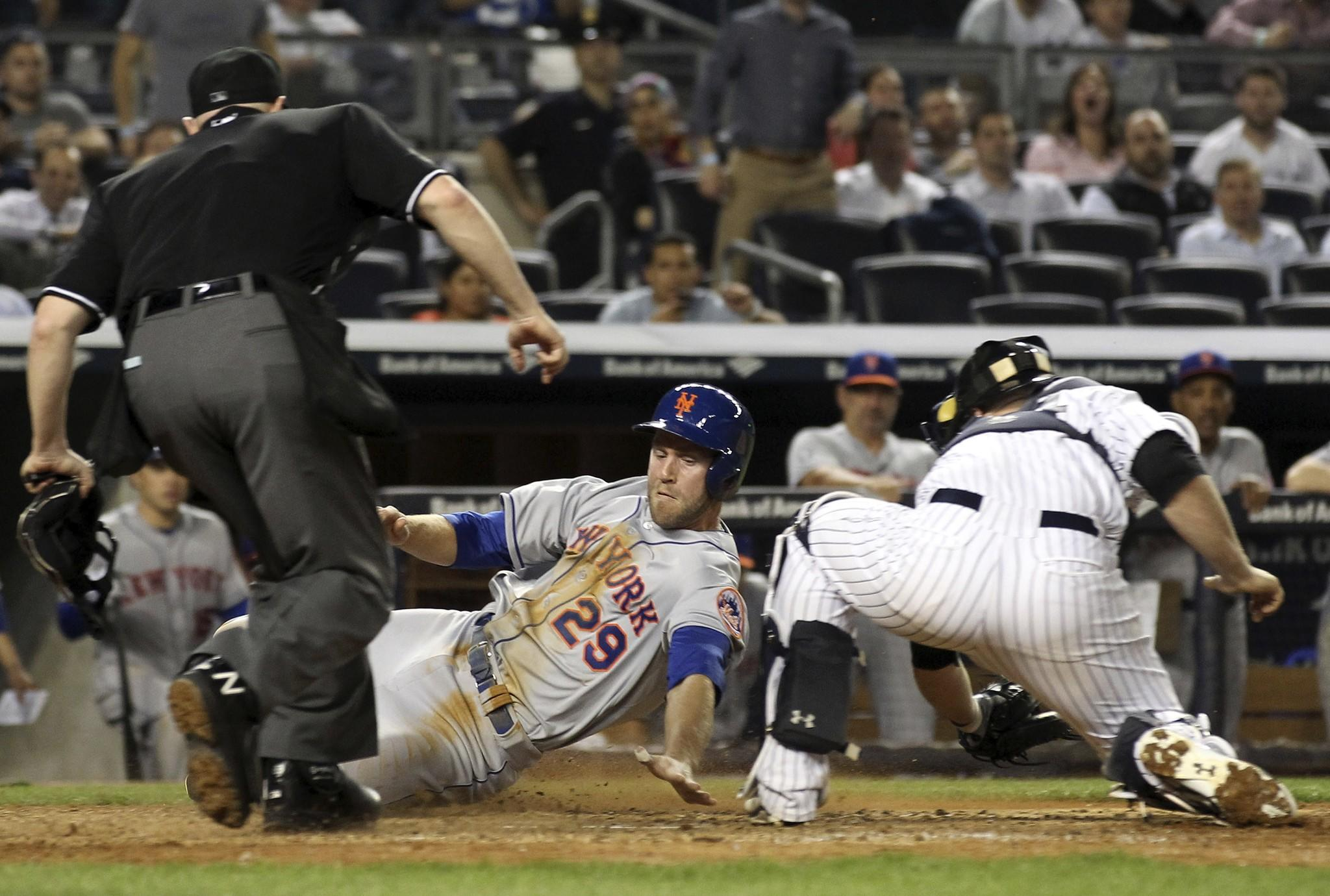 New York Mets first baseman Eric Campbell (29) scores before the tag by New York Yankees catcher Brian McCann (34) in front of home plate umpire Mike Estabrook (83) during the eighth inning at Yankee Stadium.