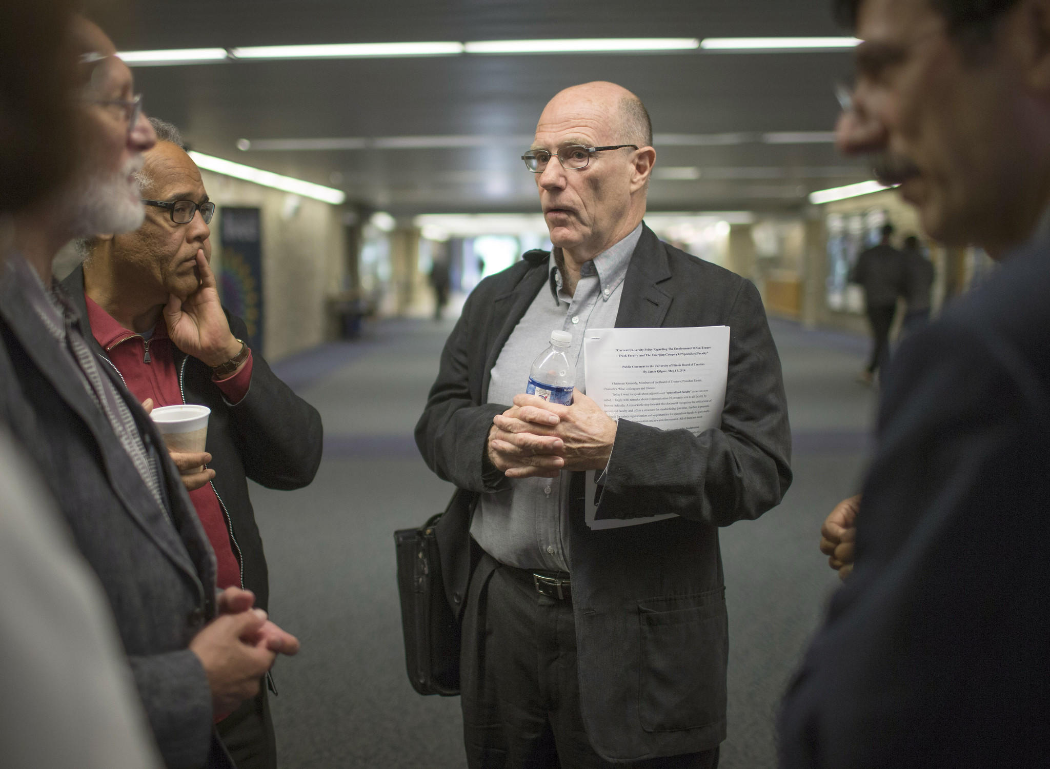 James Kilgore, center, speaks to colleagues after a board meeting at the University of Illinois Springfield campus.