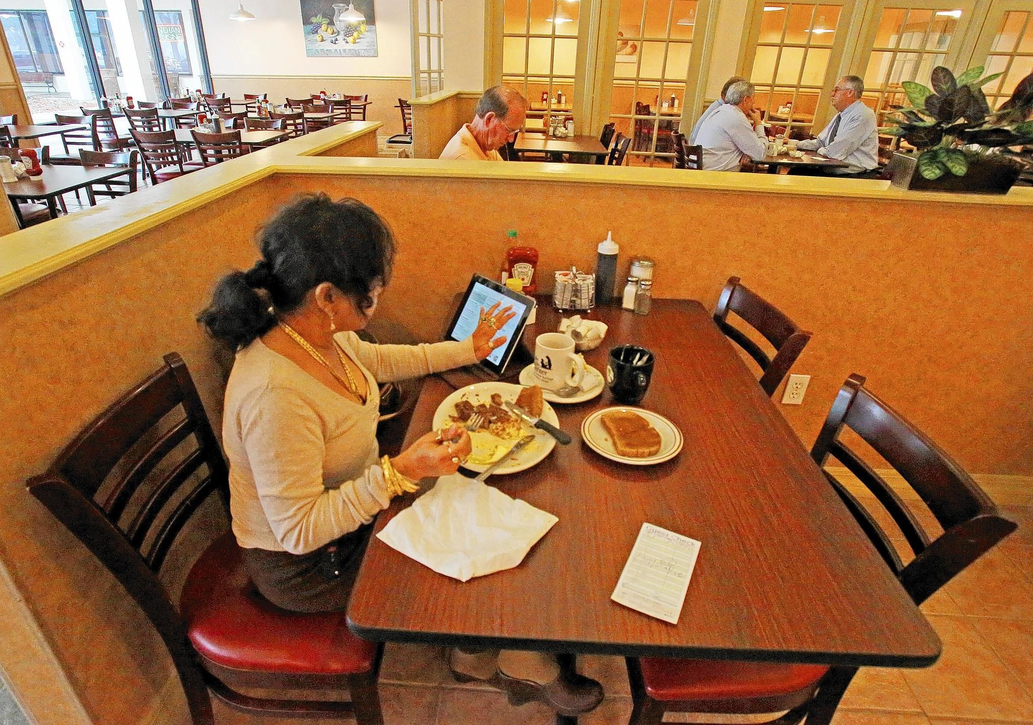 Ninia Higgins of Orlando catches up on email as she eats at The Breakfast Club in Atamonte Springs.