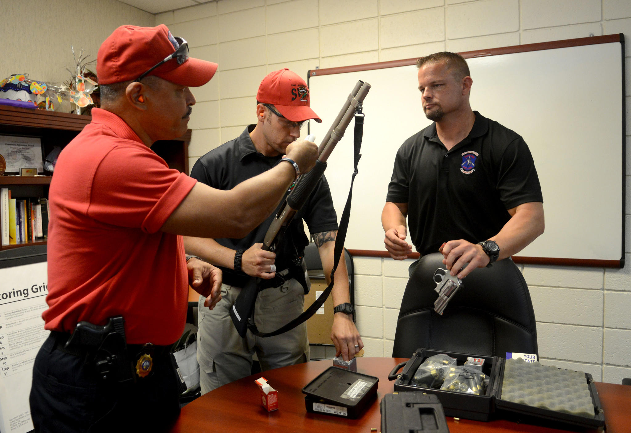 Fort Lauderdale Police Detective (left) Carmelo Colon, Detective Steve Smith and Detective Mike Lopinot double check that ammunition is blank before conducting a drill for an armed intruder with Fort Lauderdale Parks & Recreation employees Wednesday.
