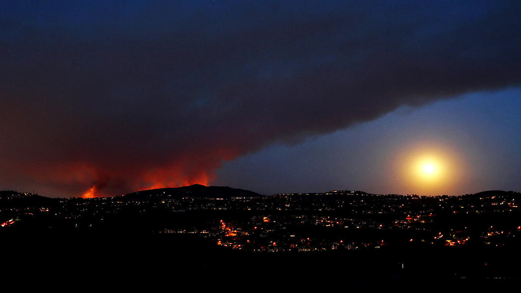 (Photographer:Luis Sinco / Los Angeles Times) - A wildfire burns in San Marcos as the moon rises in a smoky sky as seen from Carlsbad.