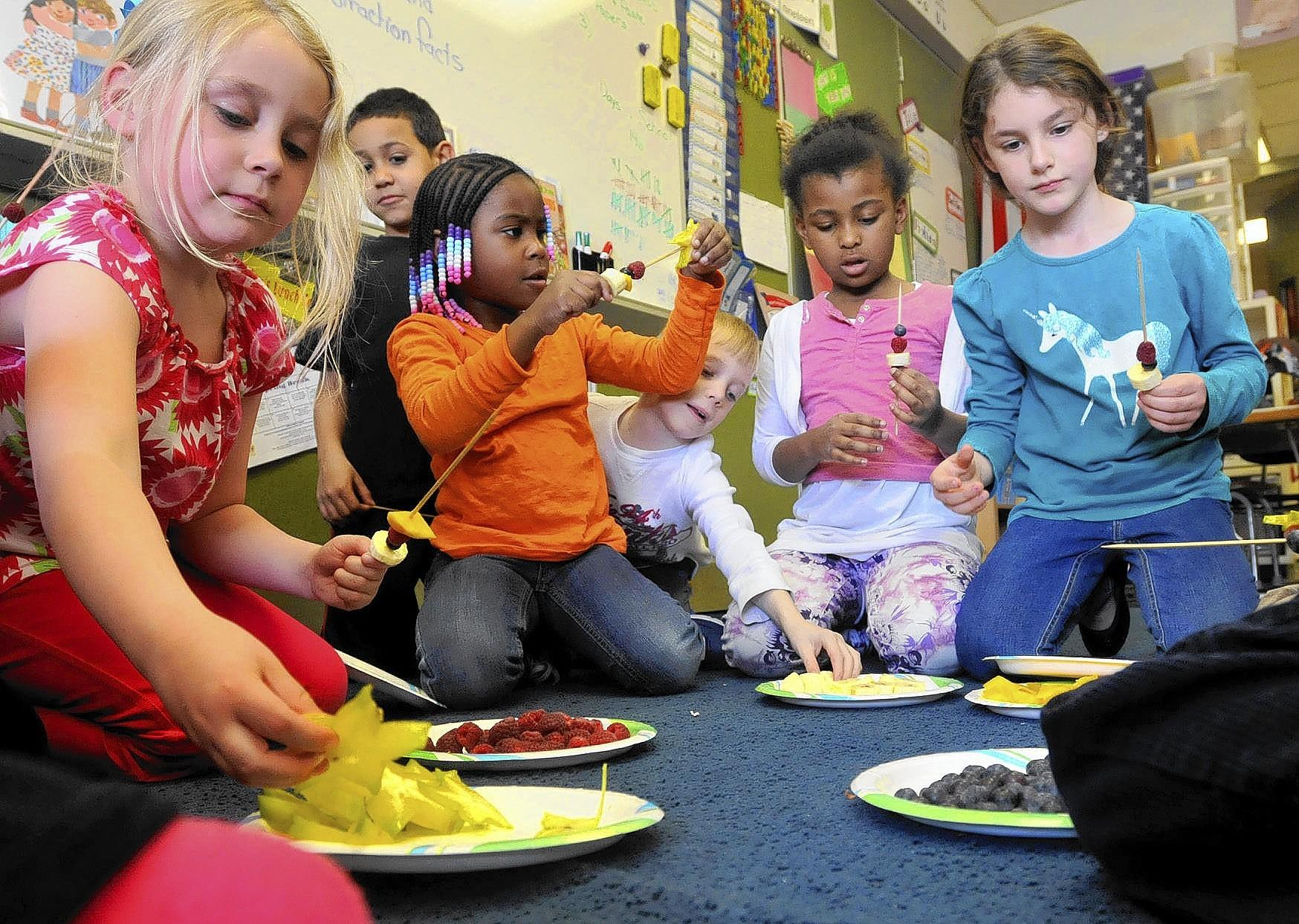 """Hartford, CT - 05/02/14 - Students are participating in an 8-week educational cluster program at Keeney School in Manchester, in which students have some say in their subject matter. Each cluster meets weekly. Left to right, kindergarteners and first graders in a cluster called """"Taste of the Tropics"""": Zoe Syme, Derrick Sheets, Ashanti Channer, Christopher Santostefano, Jazlenne Frederick and Emma Skoog make fruit magic wands. Photo by BRAD HORRIGAN 
