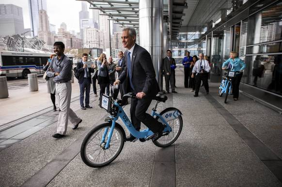 Mayor Rahm Emanuel rides a Divvy bike in front of the Blue Cross Blue Shield of Illinois building after announcing a new partnership to support Divvy bike share and bicycling programs in Chicago.