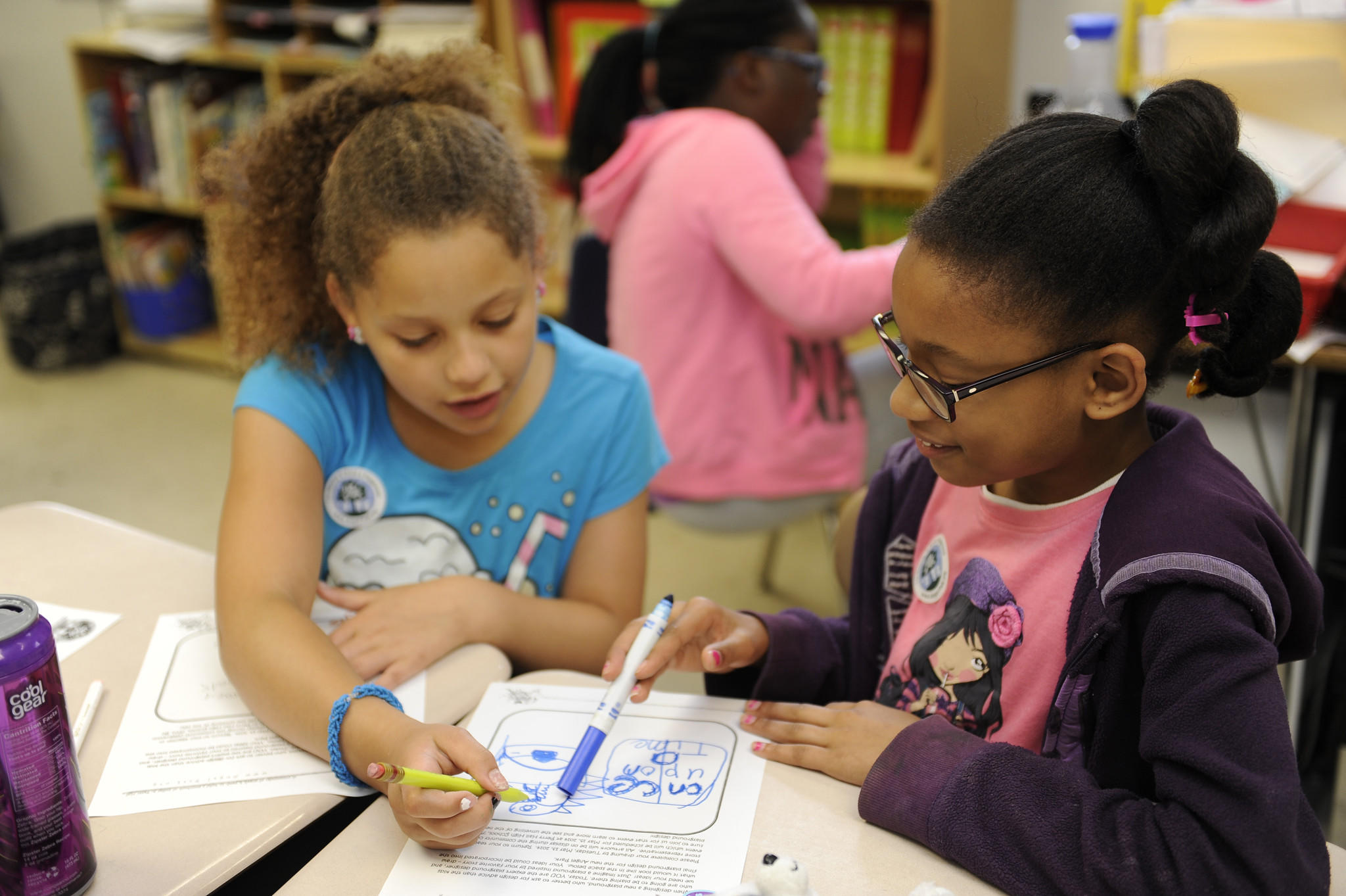 """Students at Perry Hall Elementary School are helping to design a playground called """"Angel Park."""" Today some of them did drawings of things they'd like to see at the playground. Here, Miah Bell, left, and Madison Marin look at a drawing."""