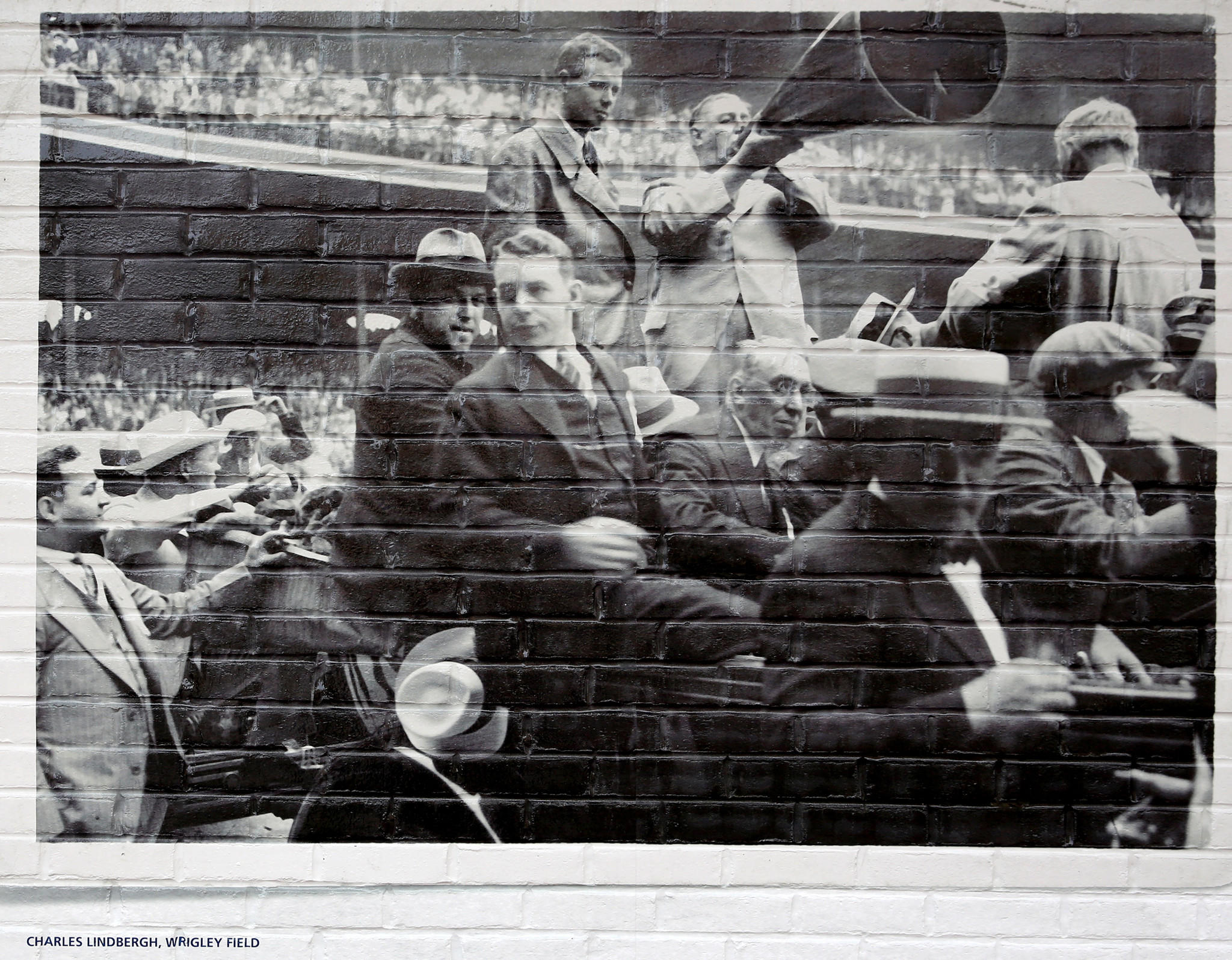 Wrigley Field in Chicago is celebrating their 100 year anniversary and they put up historic photos onto the brick on Waveland Avenue. One of the murals, a photo of Charles Lindbergh visiting Wrigley Field, is said to actually be of Comiskey Park.