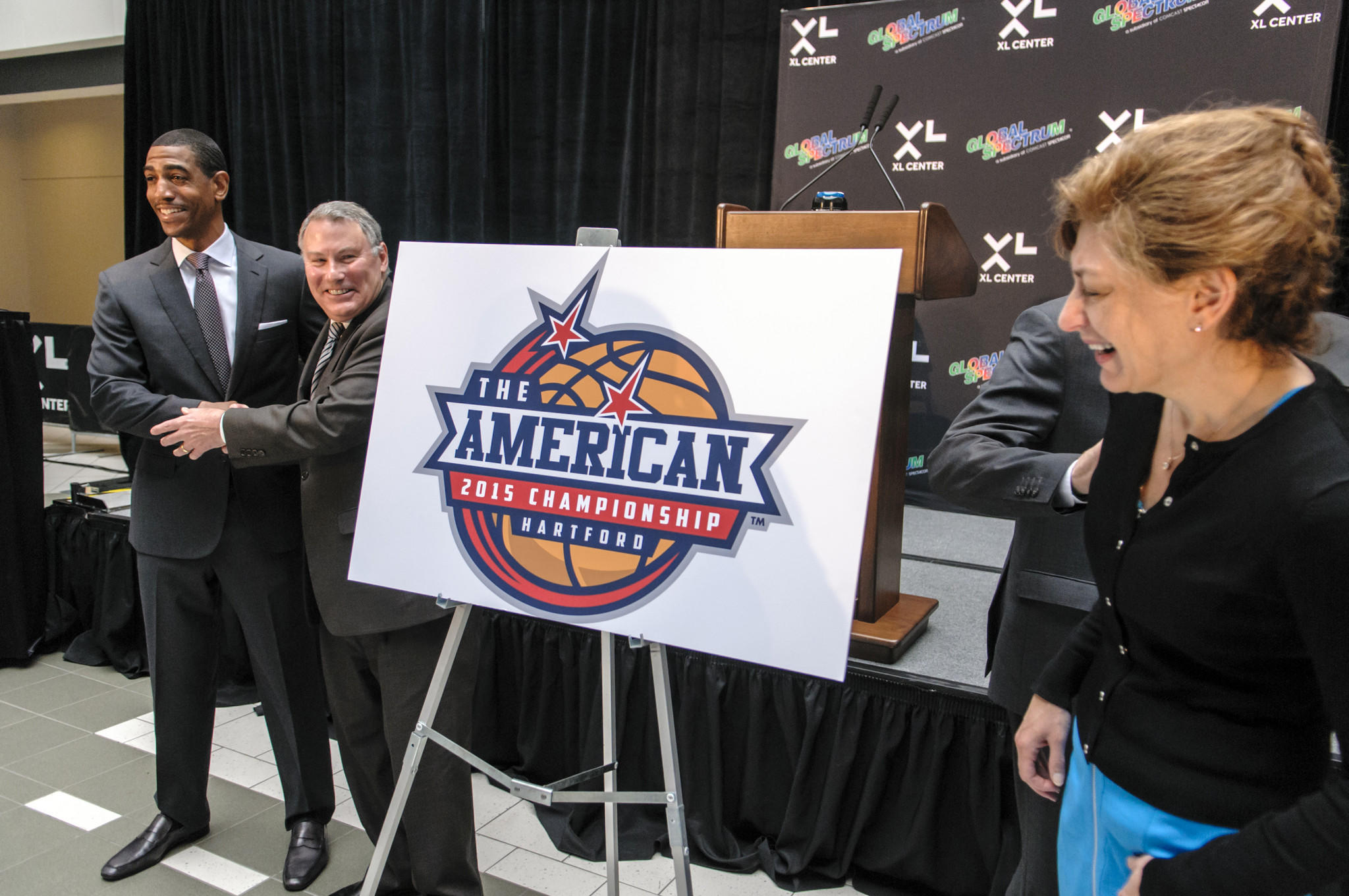 After an XL Center press conference, (L-R) UConn Men's Basketball Coach Kevin Ollie, AAC Commissioner Mike Aresco and UConn President Susan Herbst stand near the newly unveiled 2015 AAC Men's Basketball Tournament logo.
