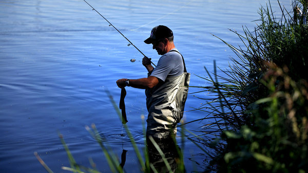 Robert Blankenship tries to unhook a sock he caught in the Los Angeles River. (Rick Loomis / Los Angeles Times)