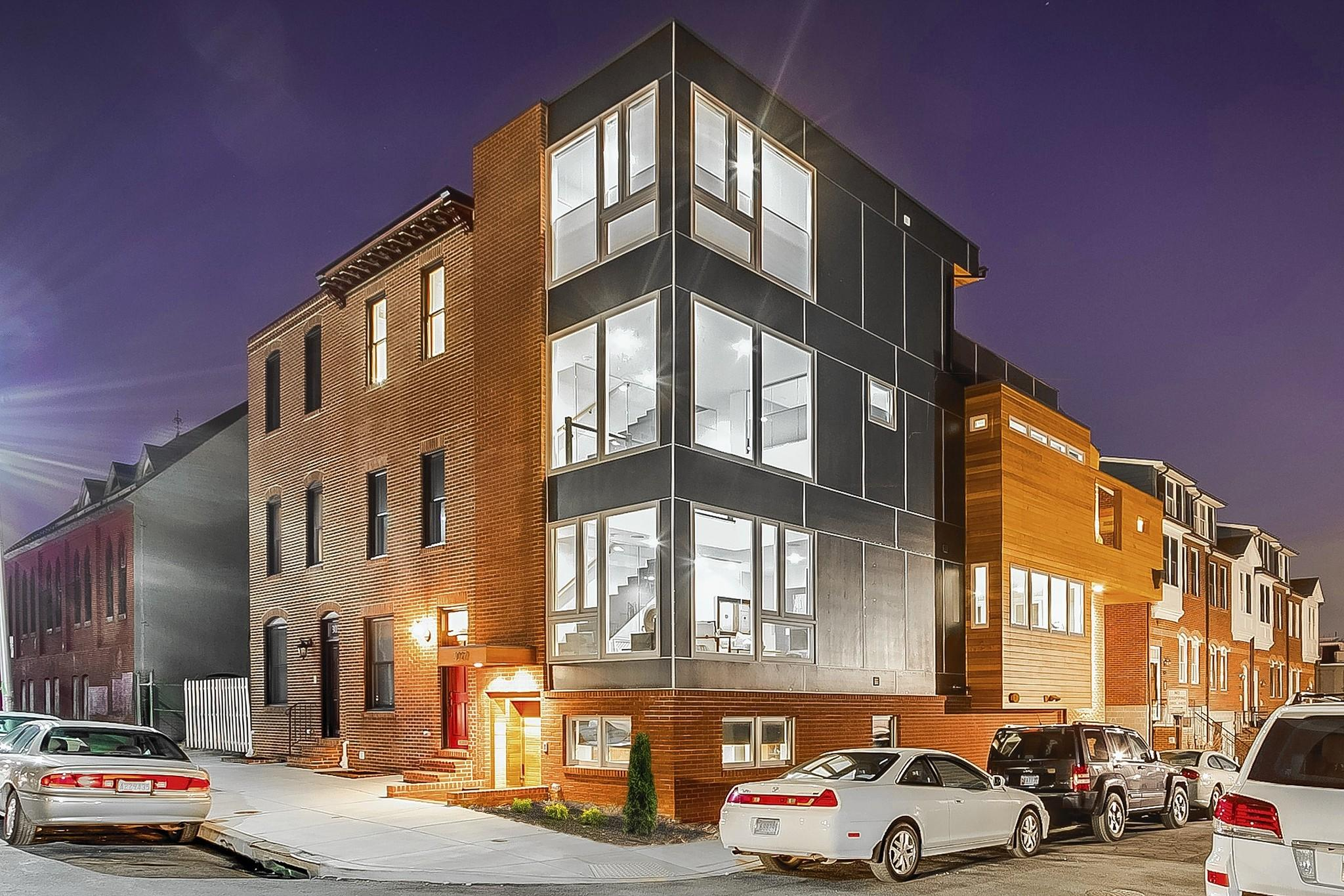 "3027 Dillon Street, Baltimore MD 21224 ""Photos by Hometrack Real Estate Marketing"" Captions: Night shot of the front of the house highlighting window walls."