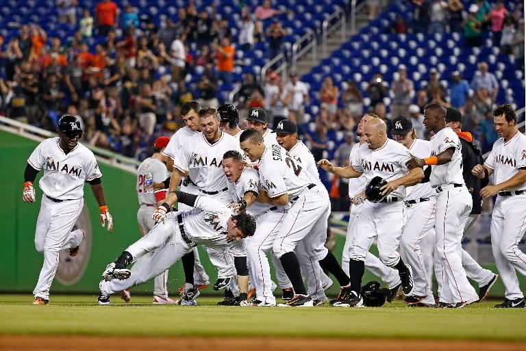 The Miami Marlins celebrate after Christian Yelich #21 (center left) hit a walk-off single during the ninth inning of the game against the Philadelphia Phillies at Marlins Park on May 22, 2014.