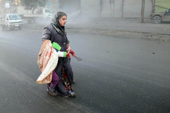 A wounded Syrian woman walks with her children after airstrikes on a rebel area of the war-torn northern city of Aleppo.