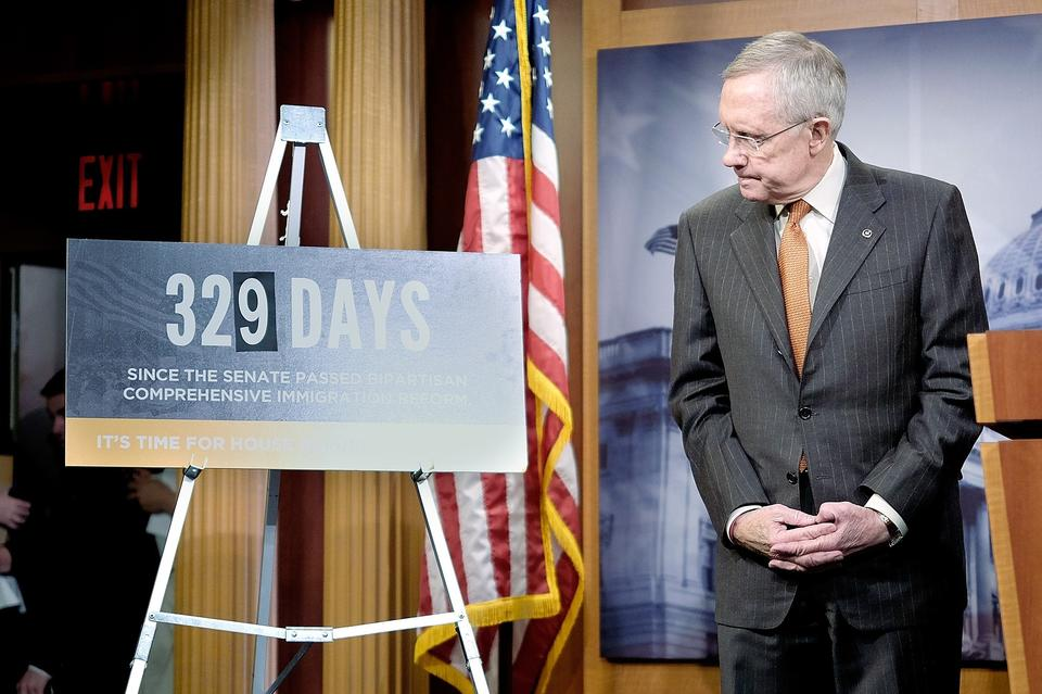 Senate Majority Leader Sen. Harry Reid (D-NV) glances at a sign counting the days since the Senate passed an immigration reform bill during a press conference with the Senate Democratic leadership at the U.S. Capitol as Senate Democrats  to urged the House to enact immigration reform and called out House Speaker John Boehner for letting nearly a year pass without taking action