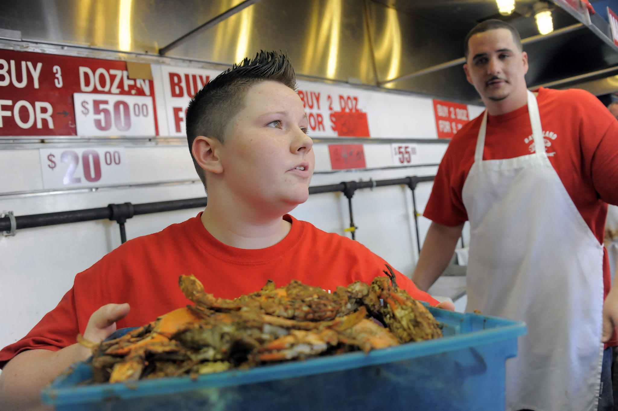 Bay Island crab house employee Michael Rickell looks at Courtney Green, who prepares to show a waiting customer the size of steamed crabs for sale Friday.