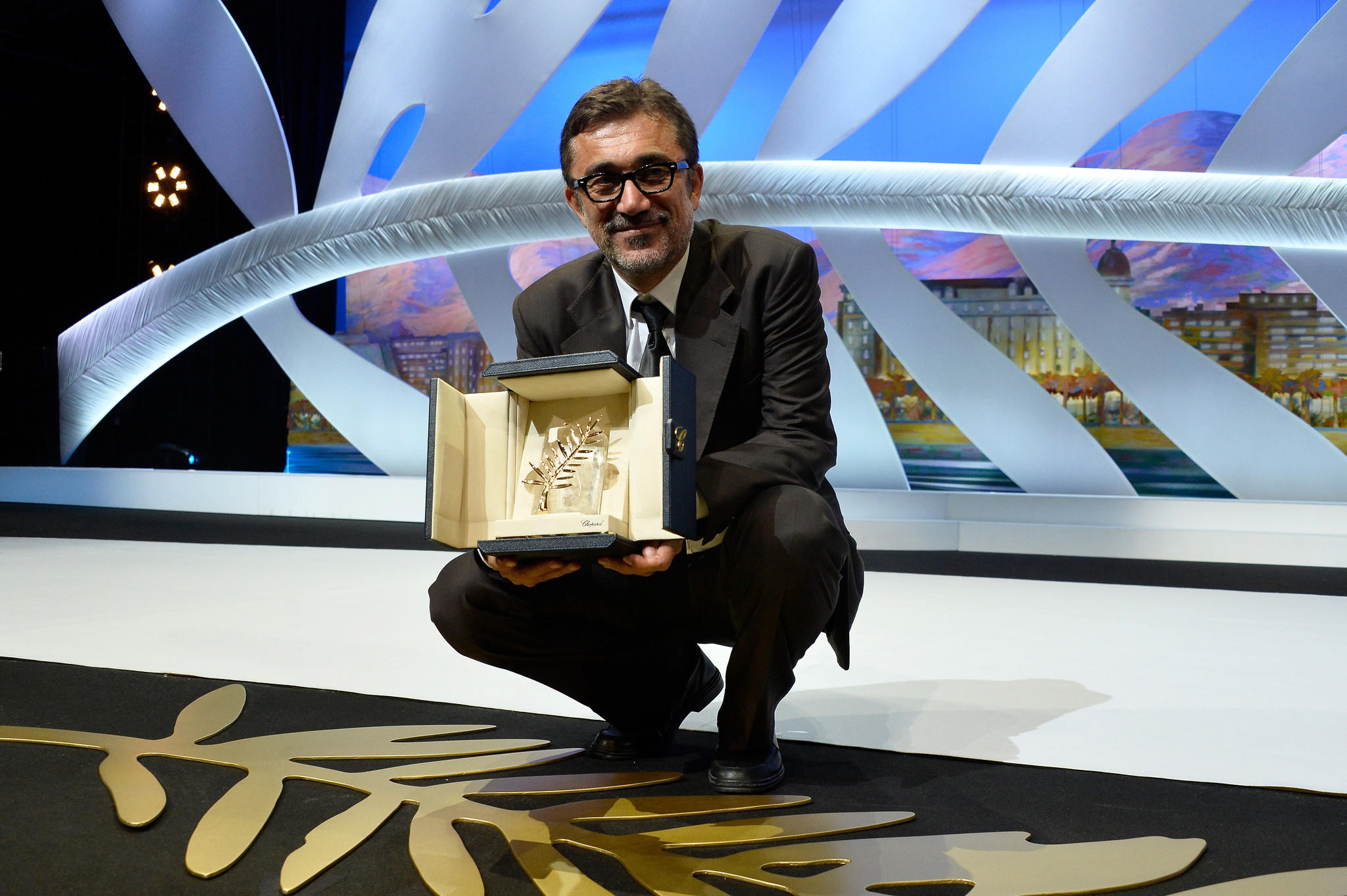 "Director Nuri Bilge Ceylan accepts the Palme d'Or award for the film ""Winter Sleep"" on stage during the Closing Ceremony at the 67th Annual Cannes Film Festival."