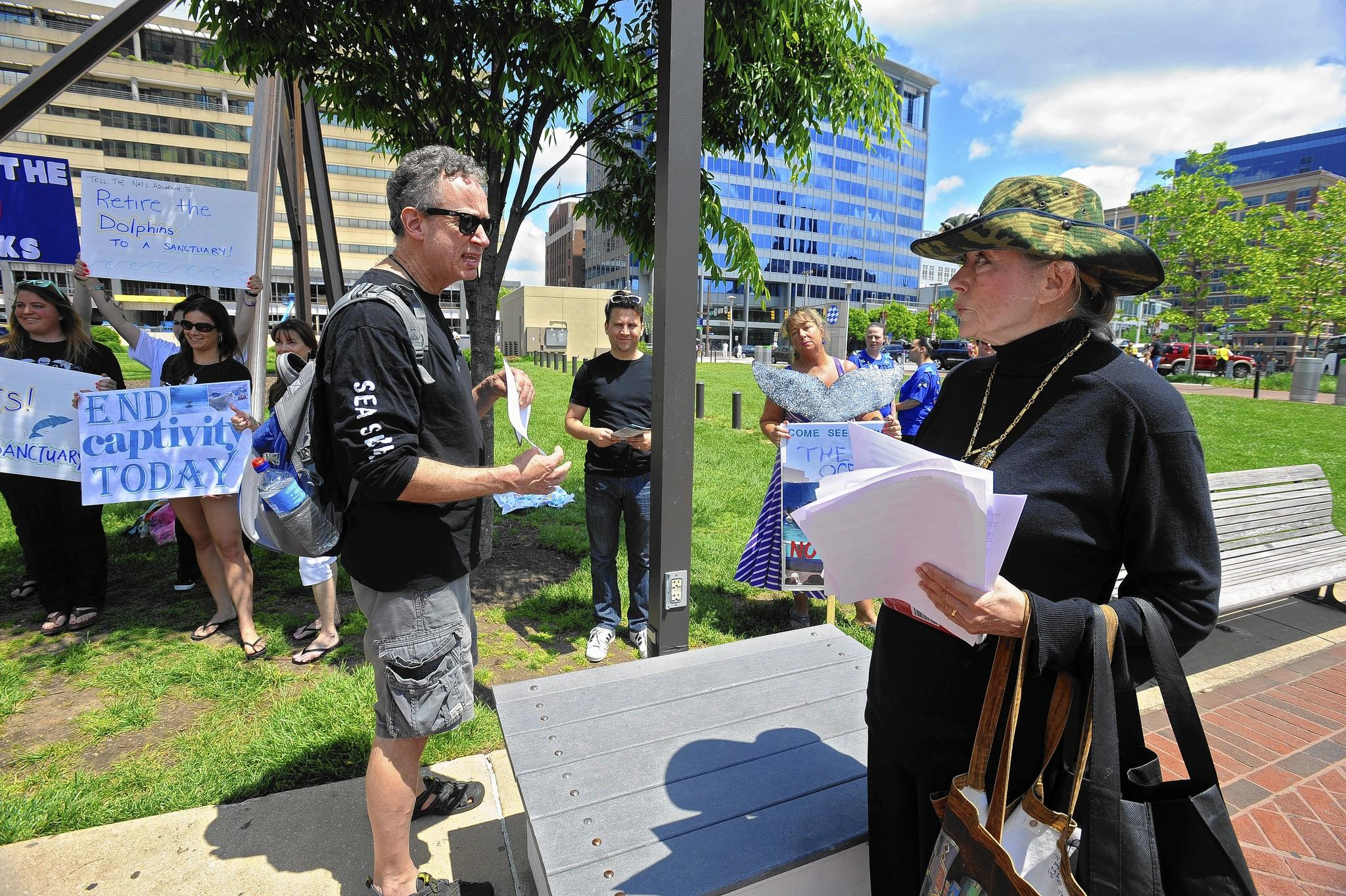 "Kevin Starbard, left, of Philadelphia, a volunteer coordinator for ""Empty the Tanks"" movement, debates Rosalind Ellis Heid, right, of the Inner Harbor Network, on the treatment of the dolphins in captivity."