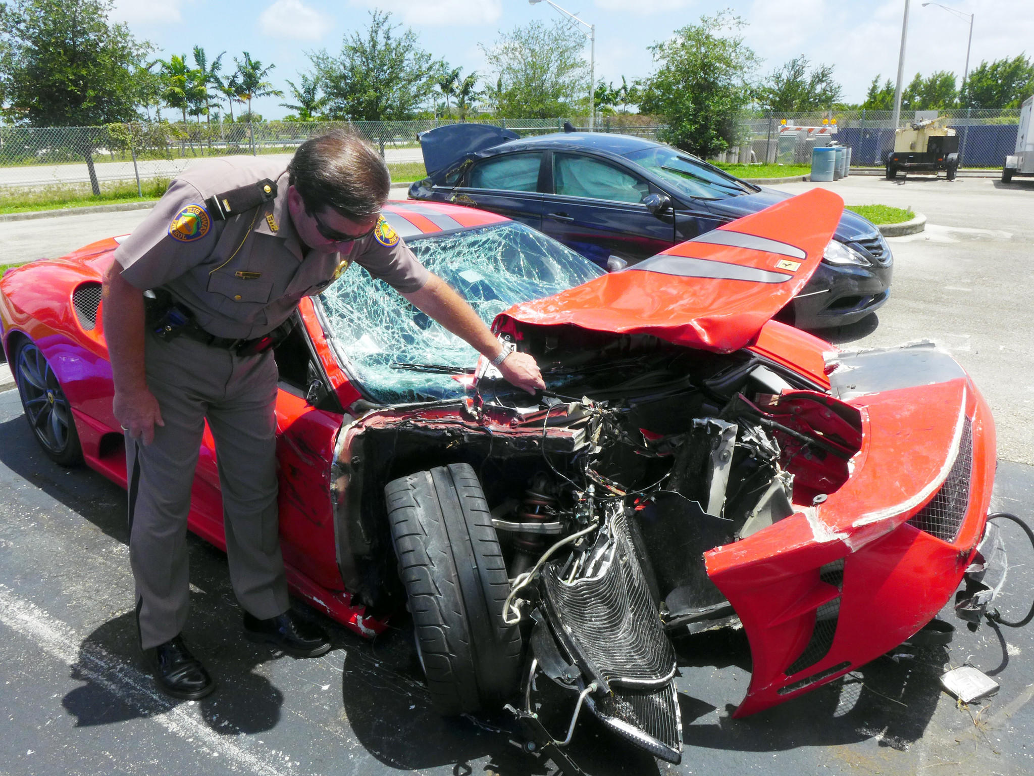 Lt. Mike Hughes of Florida Hway Patrol, checks out the damage on a Ferrari that rear-ended a Hyundai Sonata on Interstate 75. The driver of the Ferrari fled the scene.