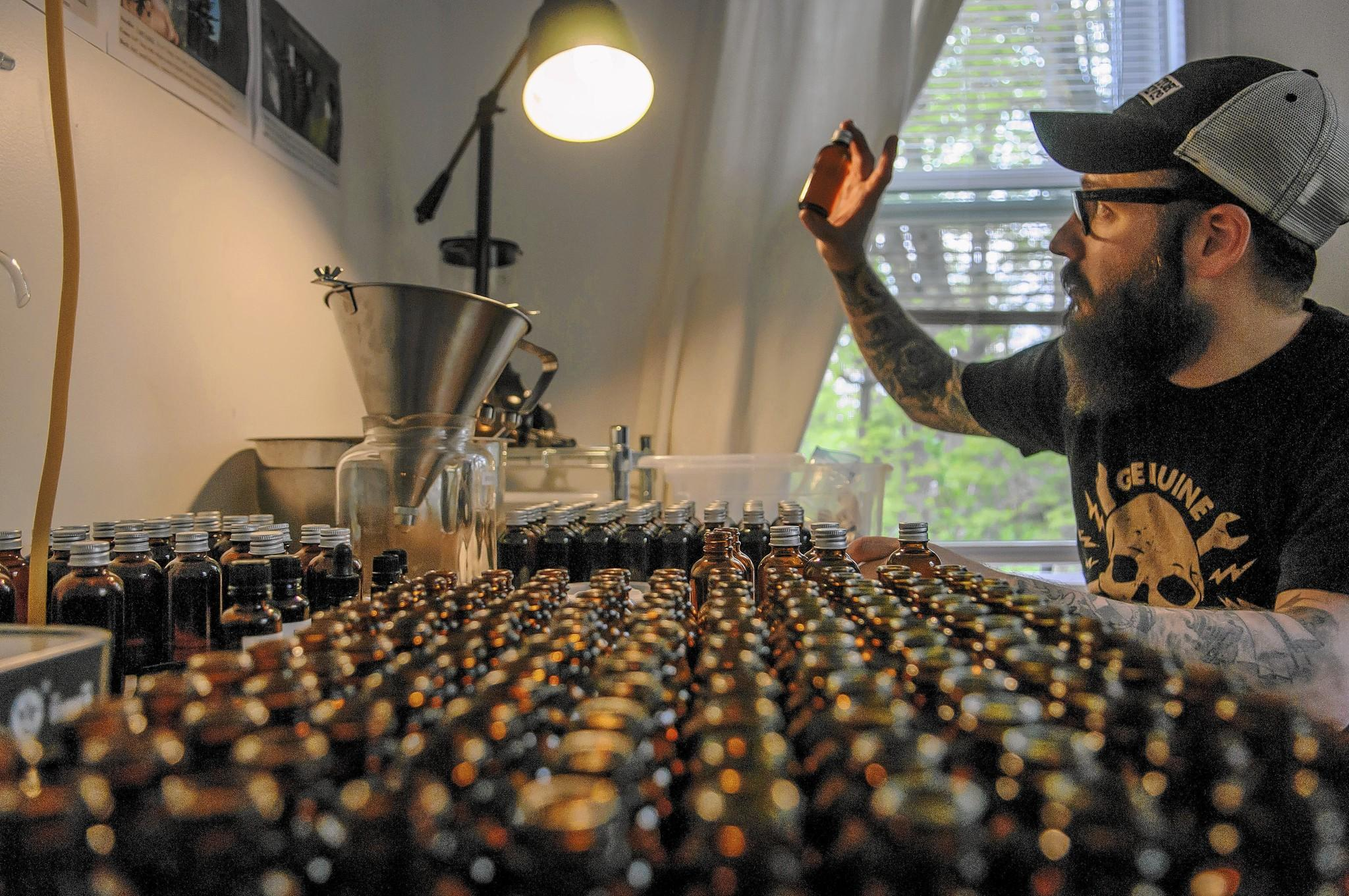 Tommy Juliano studies a shave-oil sample in his West Cornwall office and production space for his Cornwall Beard Oil.