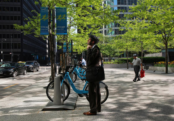 A bicyclist straps on a helmet before renting a Divvy bike on South Dearborn Street on May 21, 2014.