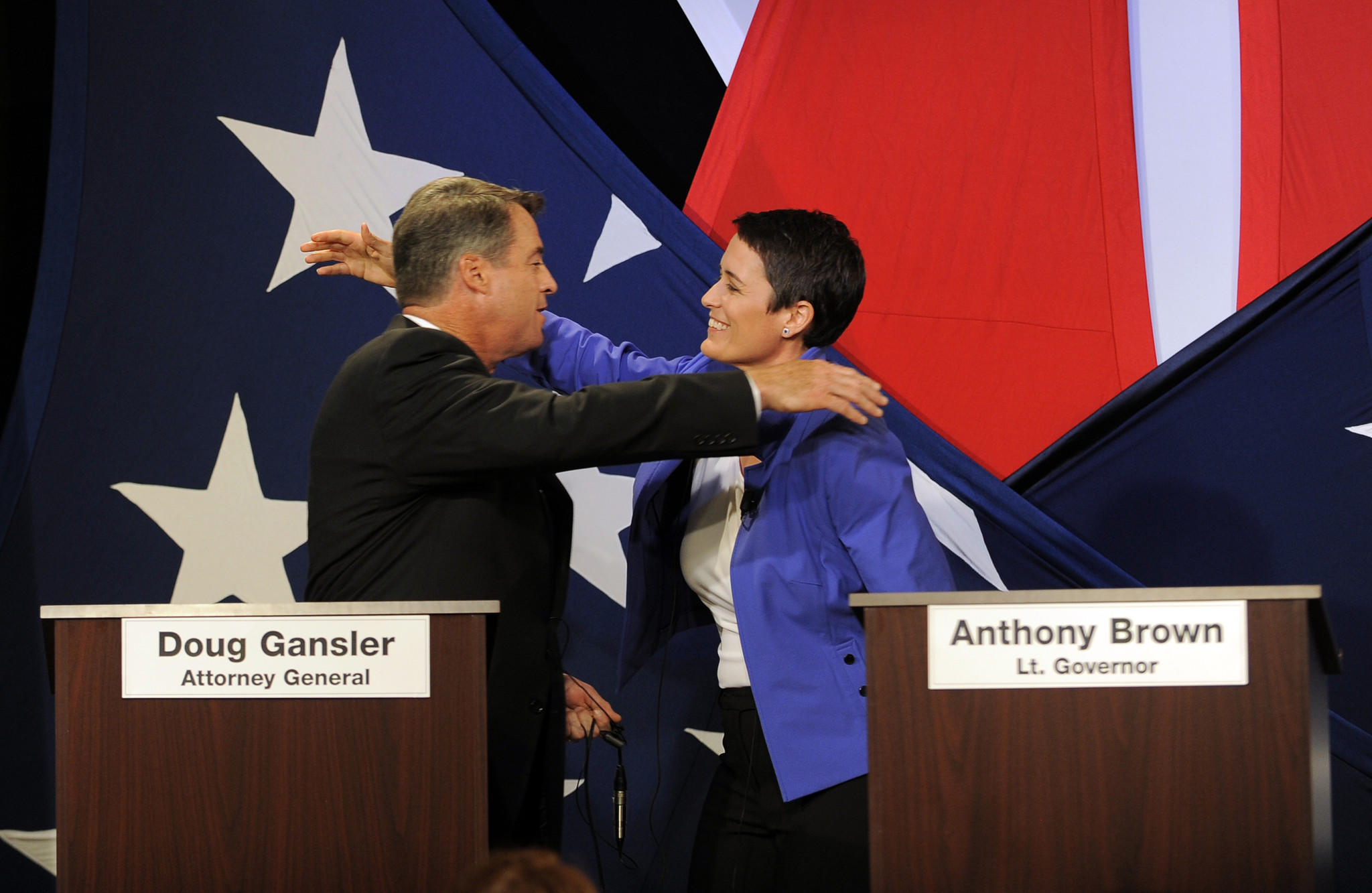 Gubernatorial candidates Attorney General Doug Gansler and Delegate Heather Mizeur embrace after debating each other across an empty podium for Lieutenant Governor Anthony Brown, who skipped the debate aired live on Fox 45.