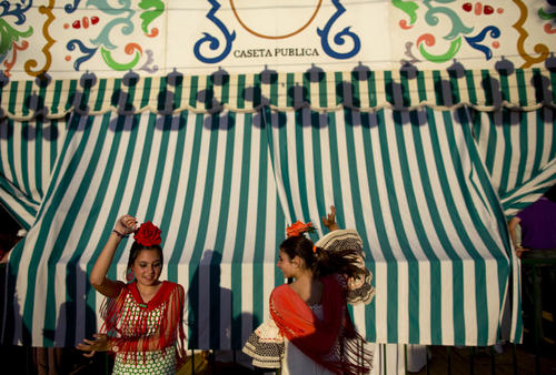 Girls wearing Sevillana dresses dance during the traditional Feria de Abril (April fair) in the Andalusian capital of Seville, southern Spain, May 8, 2014.