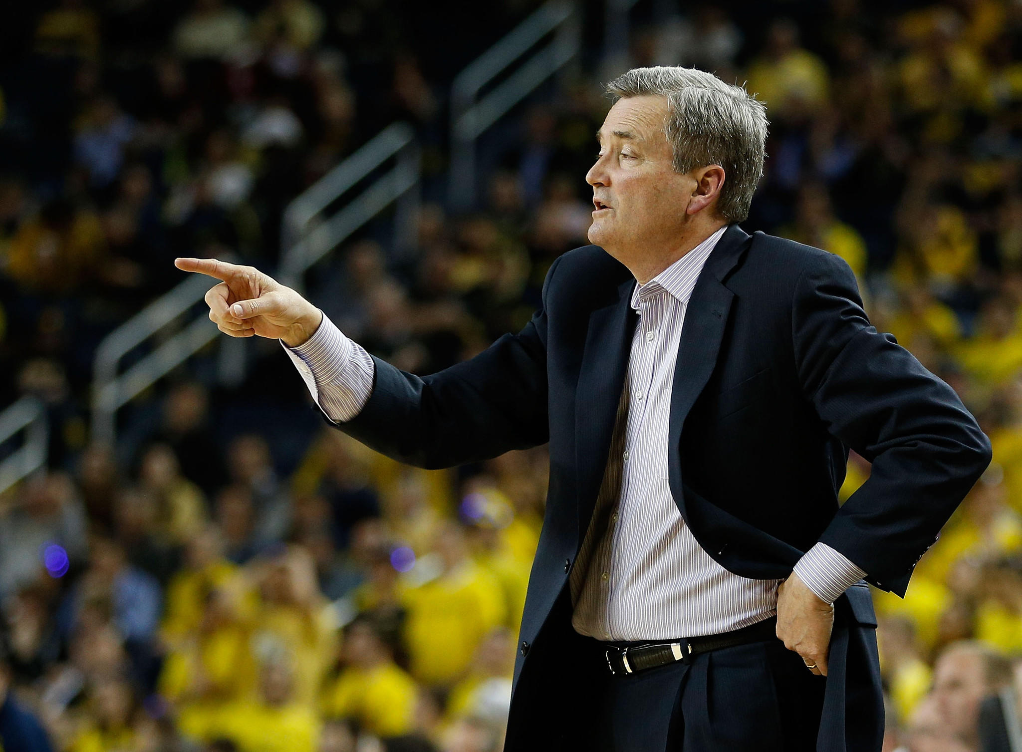 Head coach Bill Carmody of the Northwestern Wildcats points something out from the bench while playing the Michigan Wolverines at Crisler Center January 2013 in Ann Arbor, Michigan.