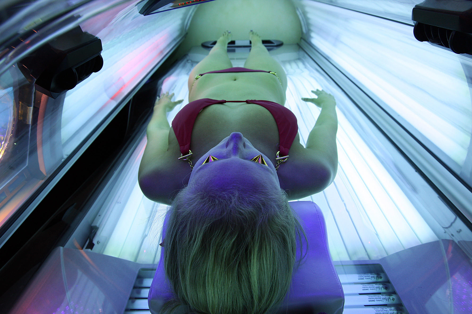 An employee of U-Tan demonstrates the workings of a tanning bed.