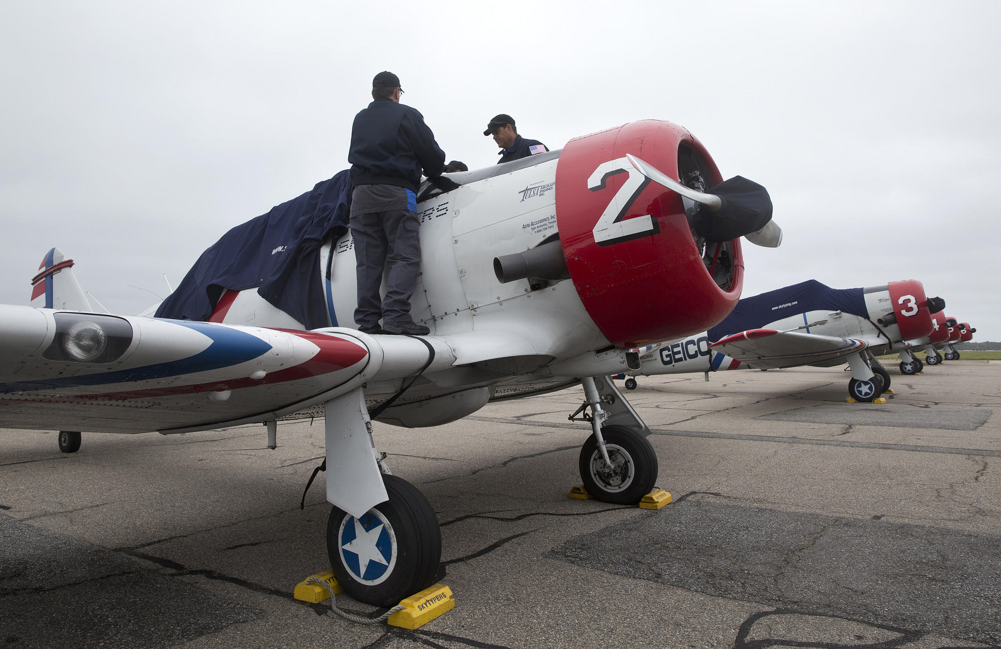 Men work on a Geico Skytypers plane at Landmark Aviation on Thursday in Norfolk.