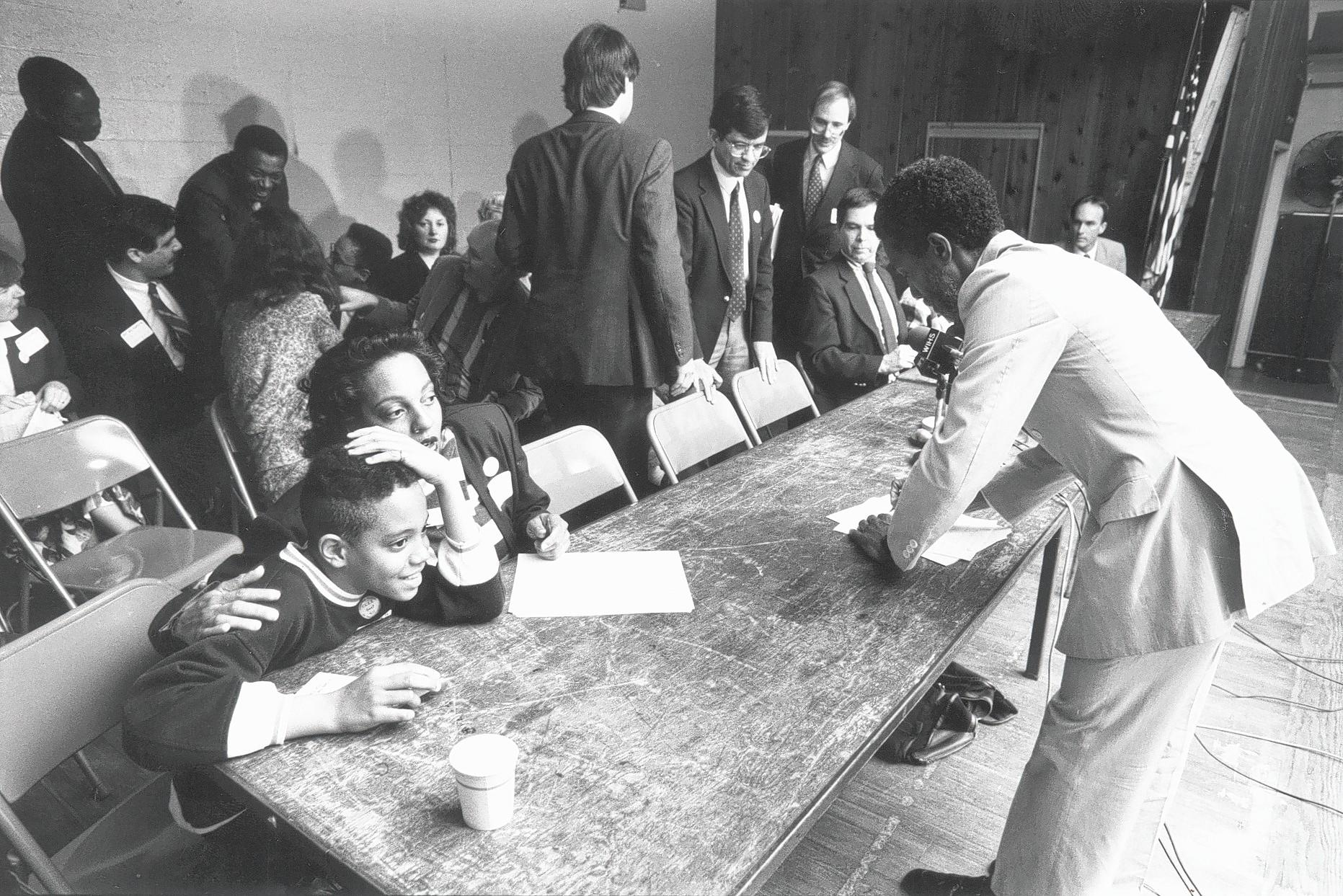 Elizabeth Sheff tries to ally the anxiety felt by her son Milo, 10, before the start of a press conference on April 27, 1989, announcing a desegregation lawsuit against the state. At right is UConn law professor John C. Brittain, one of several lawyers who argued their case.